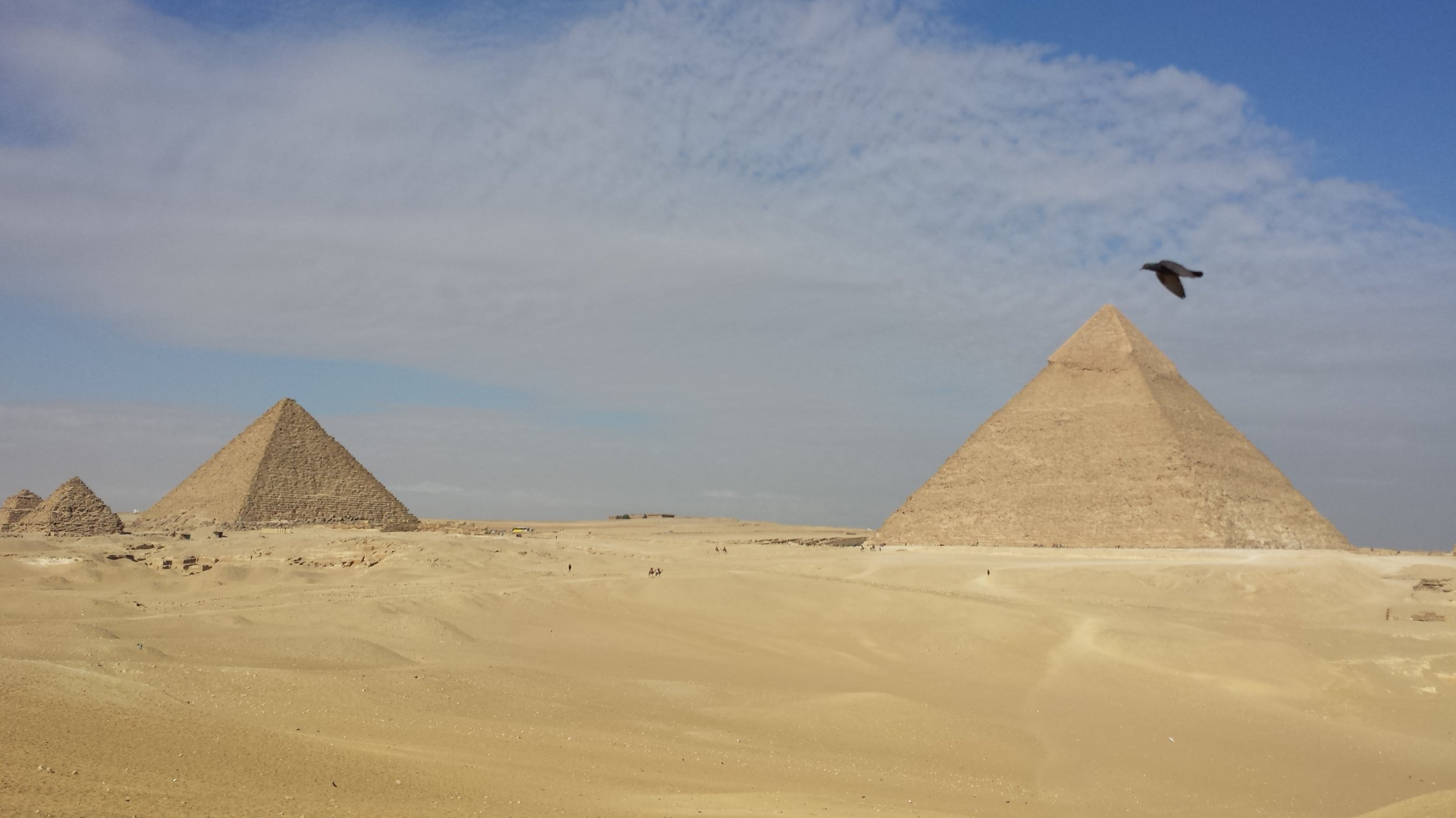 A falcon flies in front of Khafre's pyramid. Menkaure's pyramid and those of his queens are on the left.