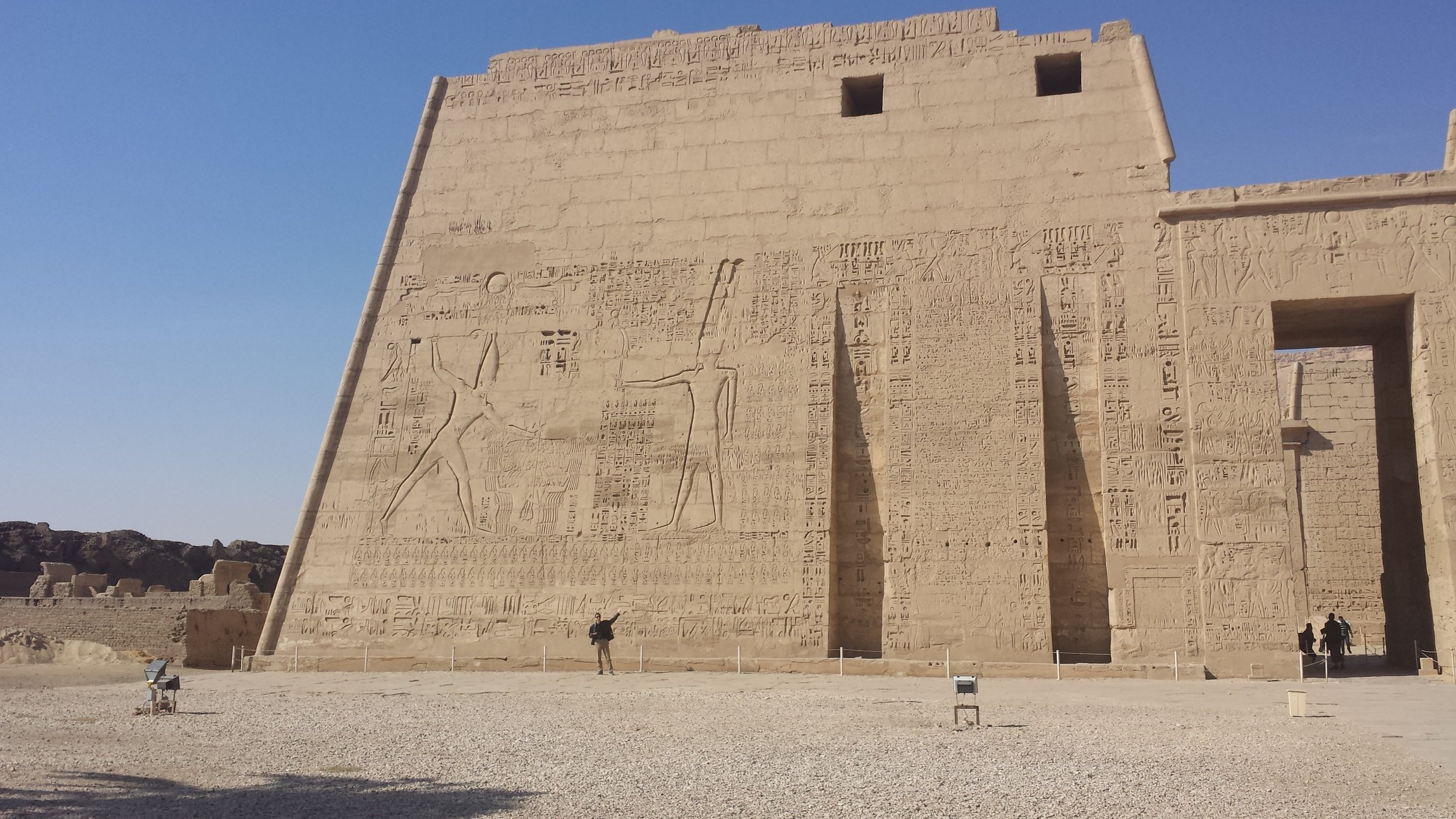 The entry pylon to Habu temple. Some fool is standing in front of it to give a sense of scale. It depicts Ramses III making offering to Ra.