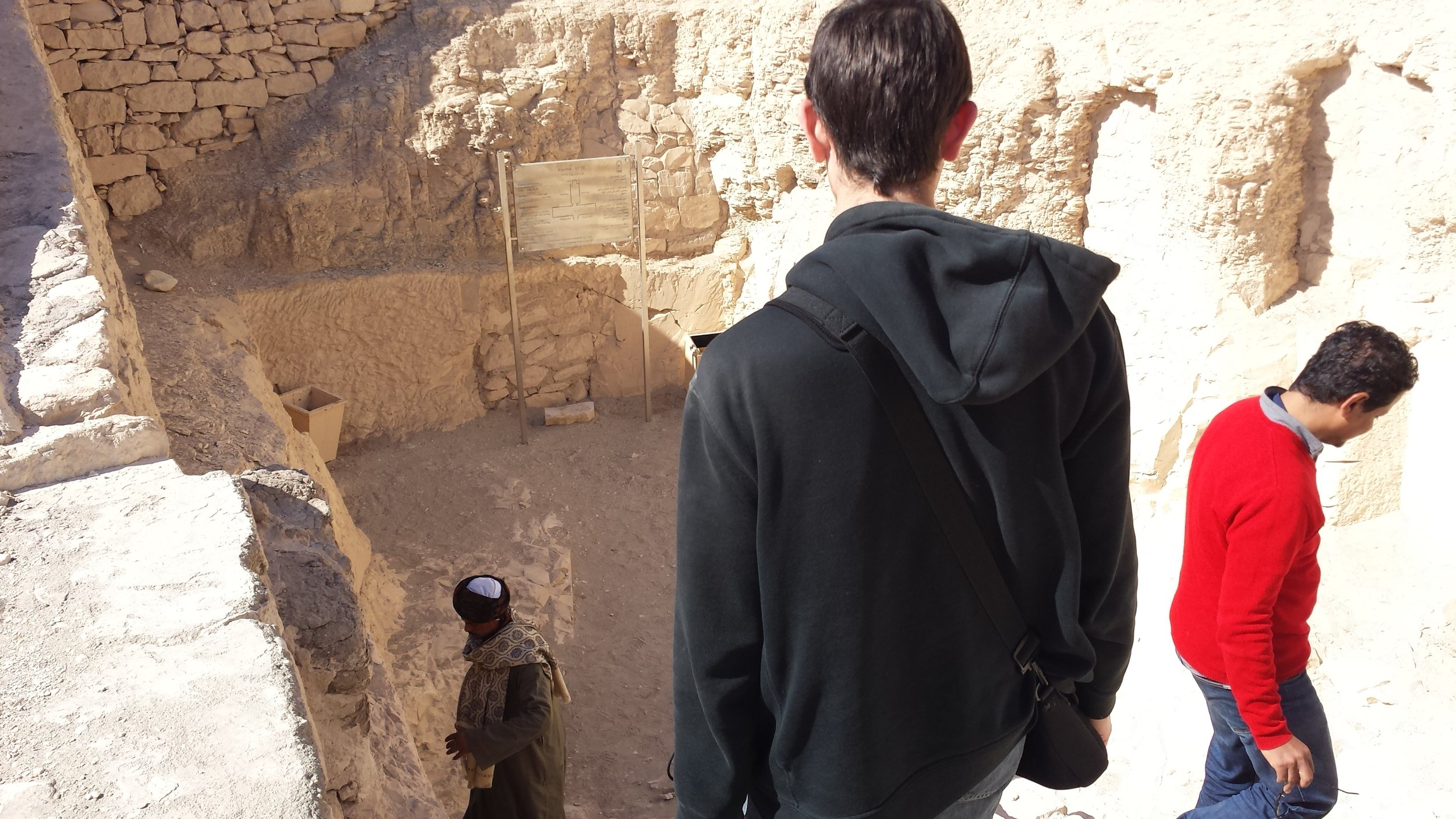 Stanley and our guide descend stairs while the guard at the bottom unlocks one of the tombs for us.