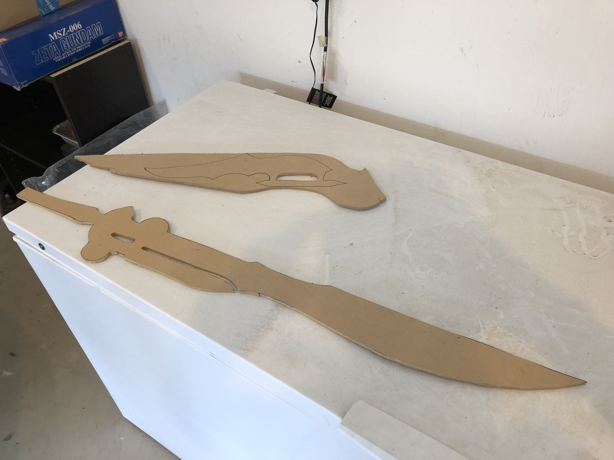 The base of both blades are MDF, and there are some wood elements for each one as well. I used a dowel that I split up the middle for the knife handle so that it would be round, and I used thin plywood pieces for details on the sword, to help with stability.