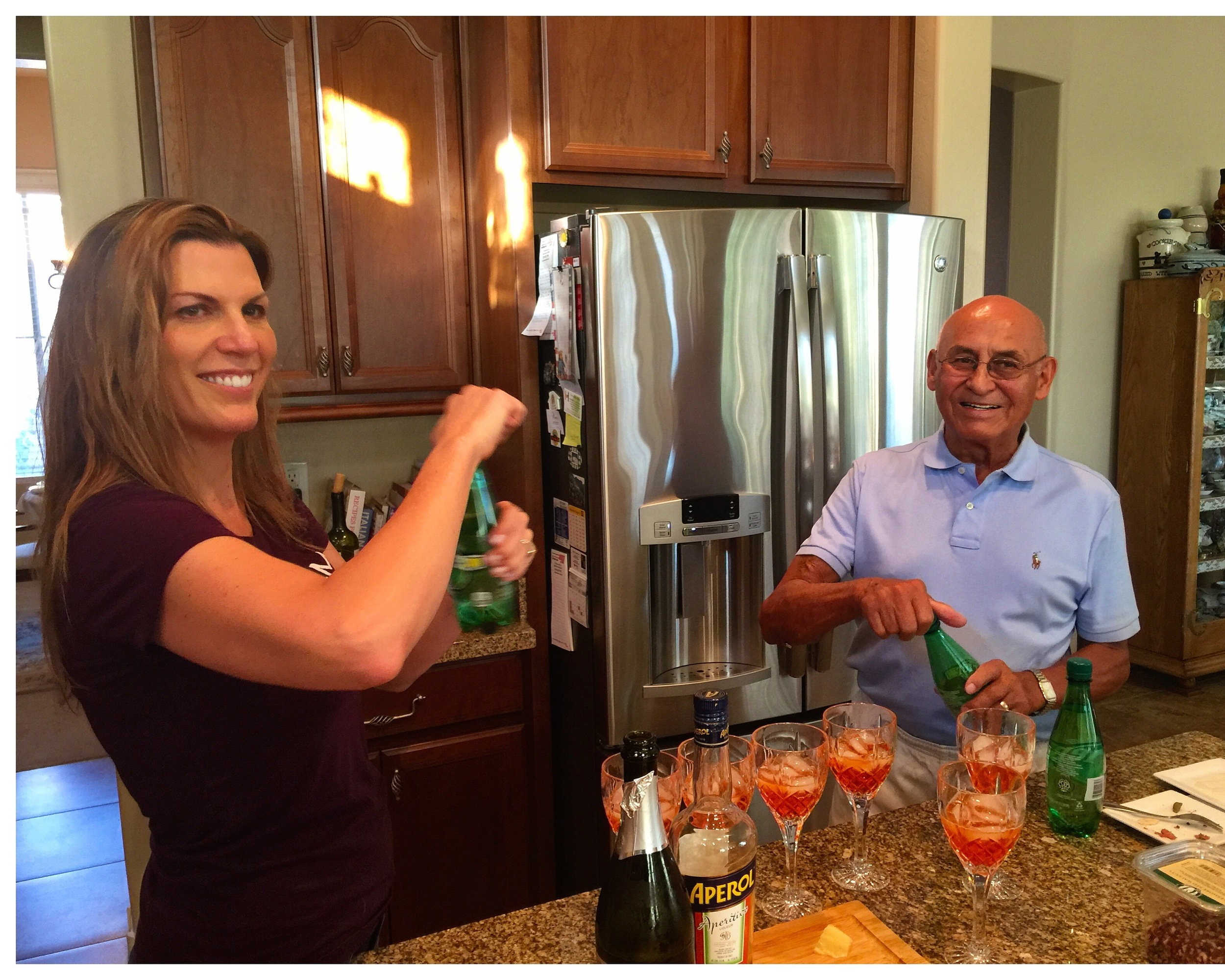 Isabel fixing Aperol Spritzs with Grandpa Don Candelaria