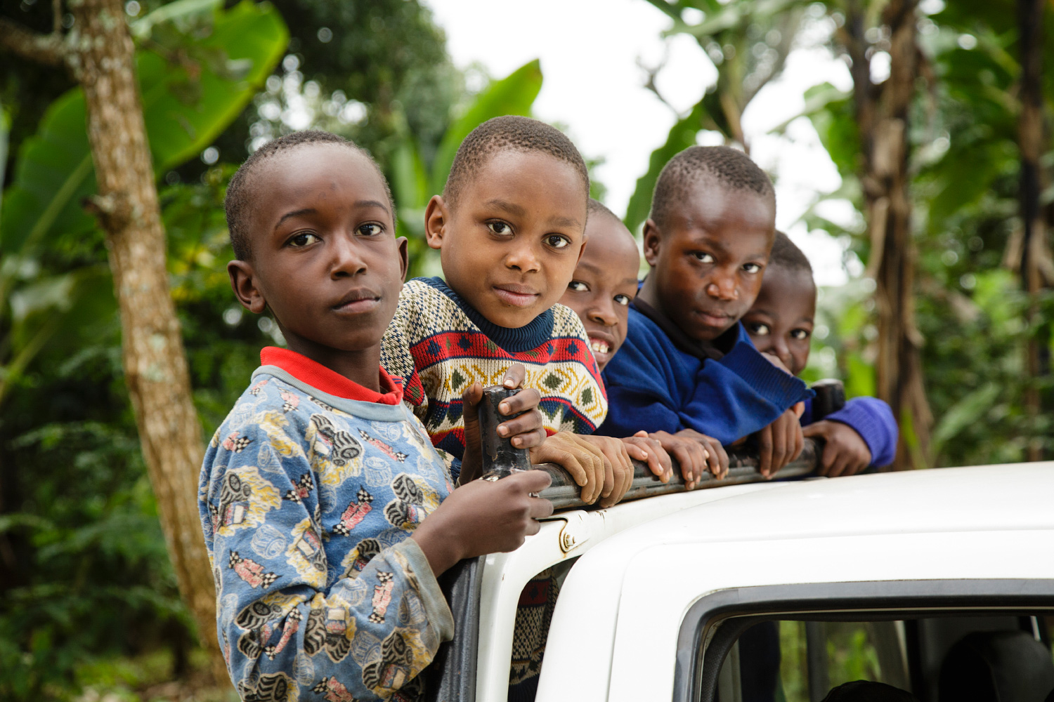 Village children riding on the back of a car in Kibosho-Umbwe.