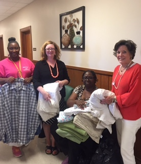 Candace Chase (left), emergency assistant/volunteer coordinator at St. Gabriel Mercy Center; Heather Miller, the Delta Center; Mavis Honorable, SGMC assistant director; and Lee Aylward, the Delta Center, recently sorted linens donated by participants in this summer's Delta Center workshops.
