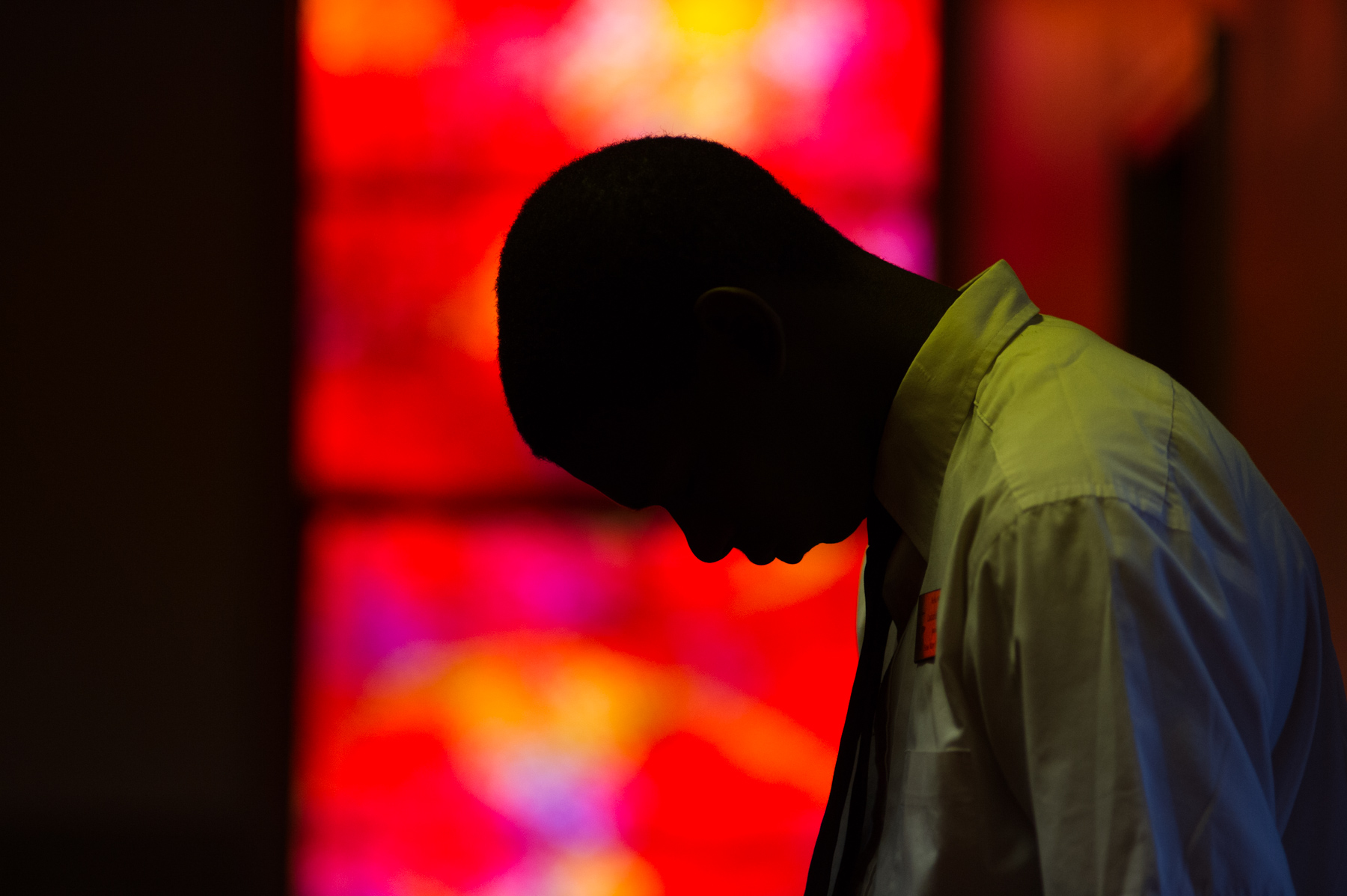 A teenage usher bows his head for prayer during church services.