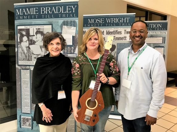 NEH Most Southern Institute participant Toni Dringman (center) from Kansas donating a guitar made by her husband to The Delta Center.
