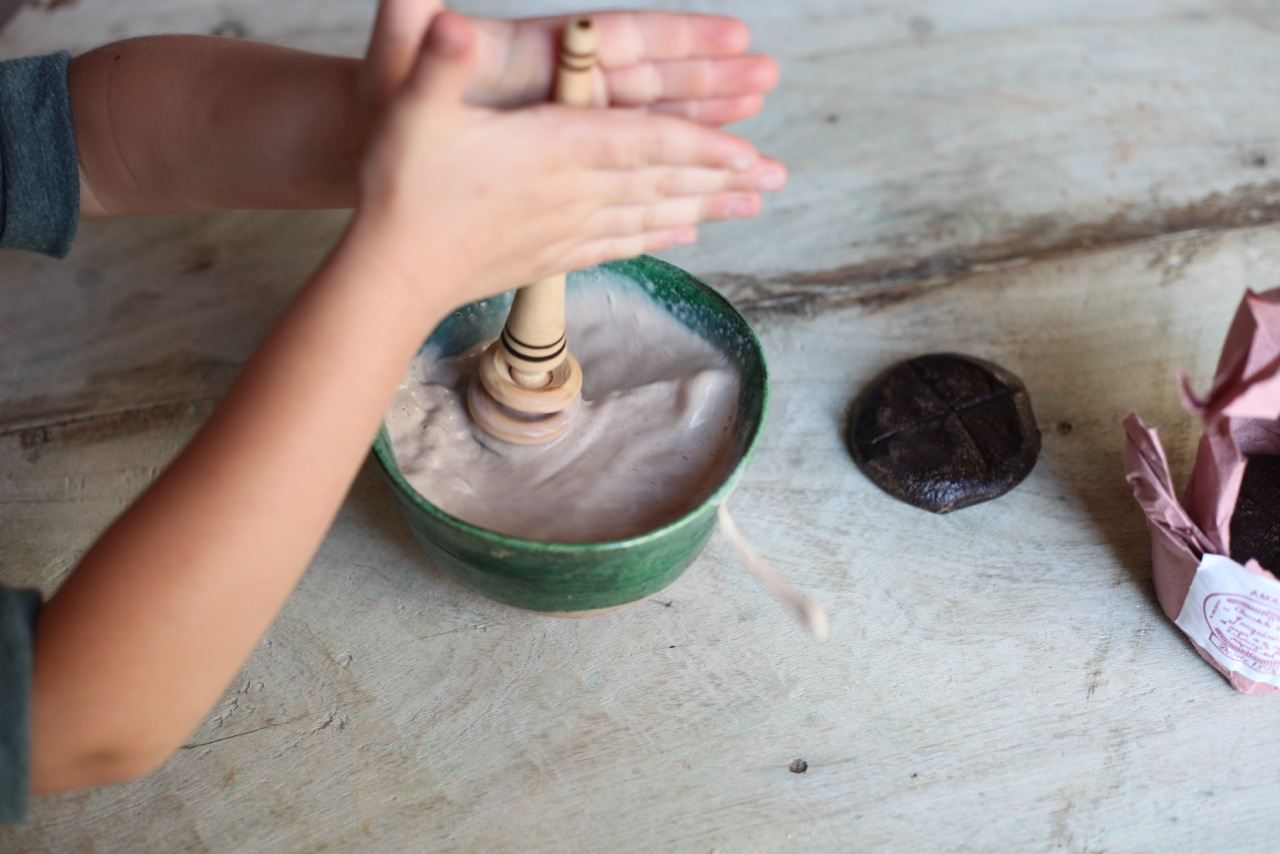 Lola demonstrating the use of the  molinillo  to incorporate the disk of chocolate into the milk. Note the use of her palms...