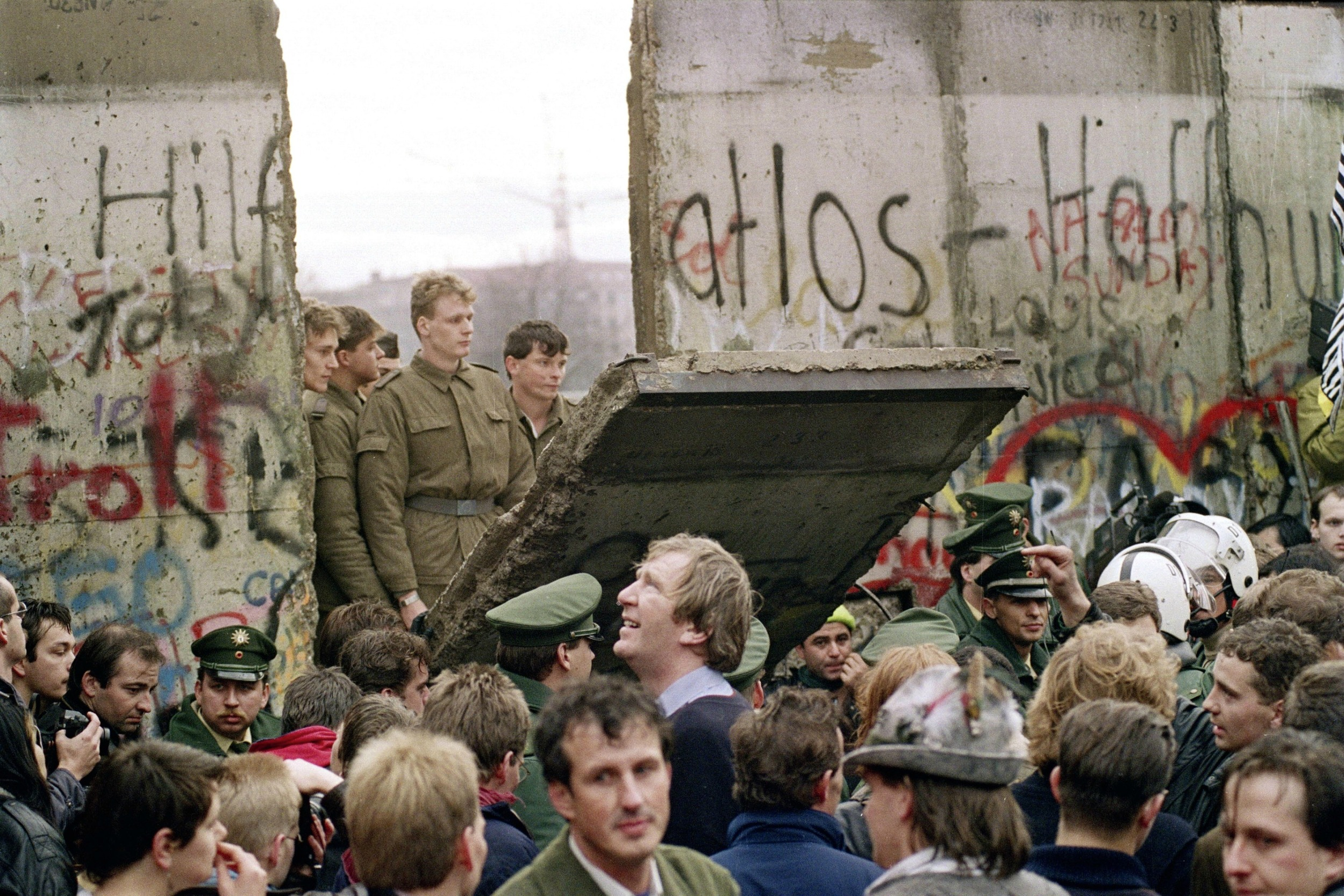 The Berlin Wall comes down - East German soldiers look on