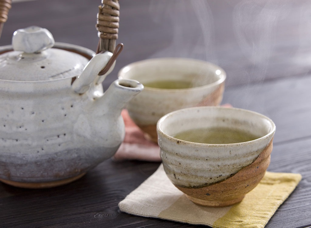 Steaming tea warms our hands in autumn.