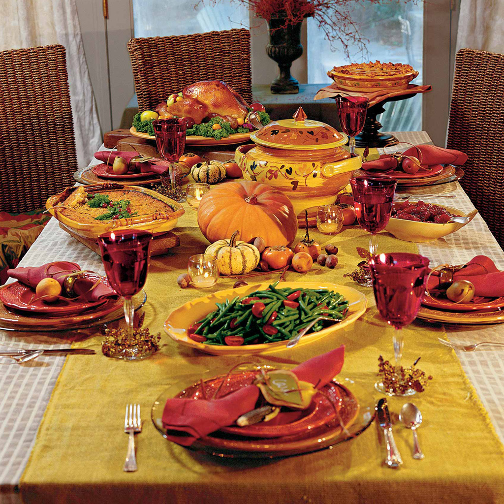 A Thanksgiving table with traditional foods such as turkey, green beans, and cranberry sauce.
