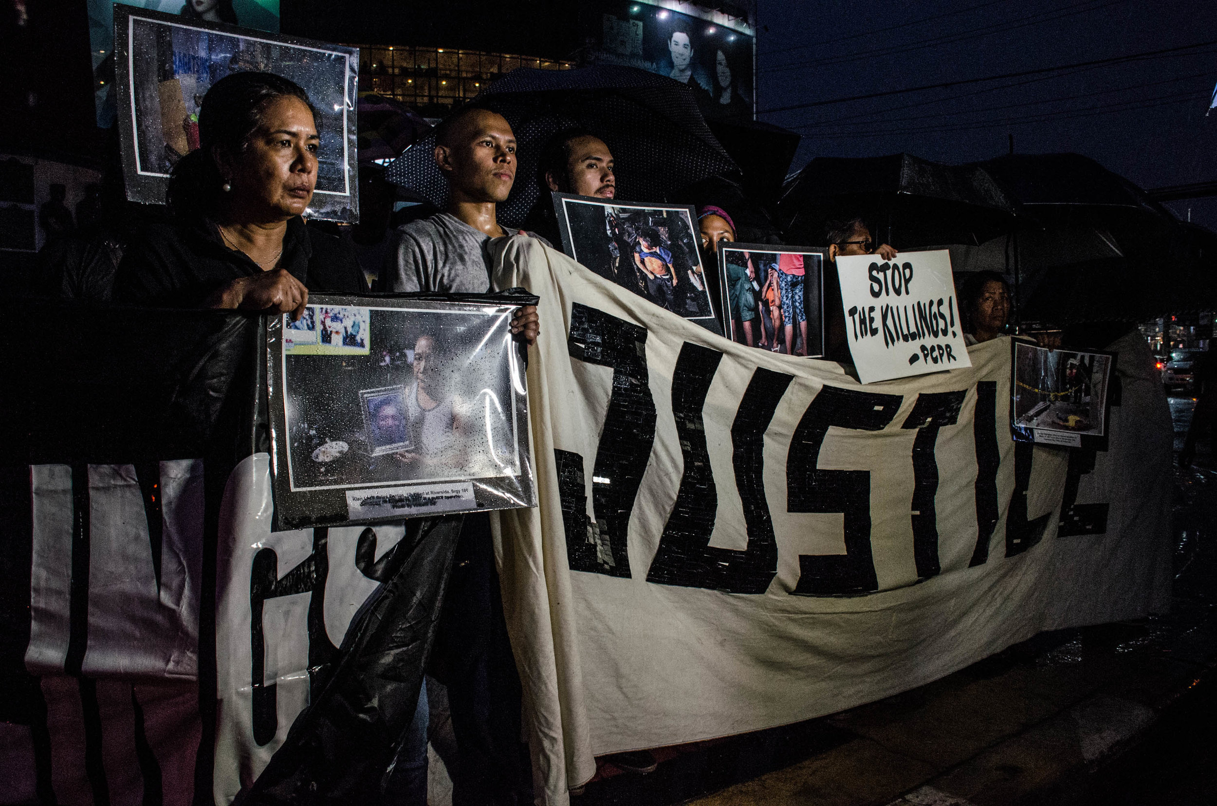 Protesters hold photos of the EJK victims and their families during a protest at the Boy Scout Monument, Quezon City.