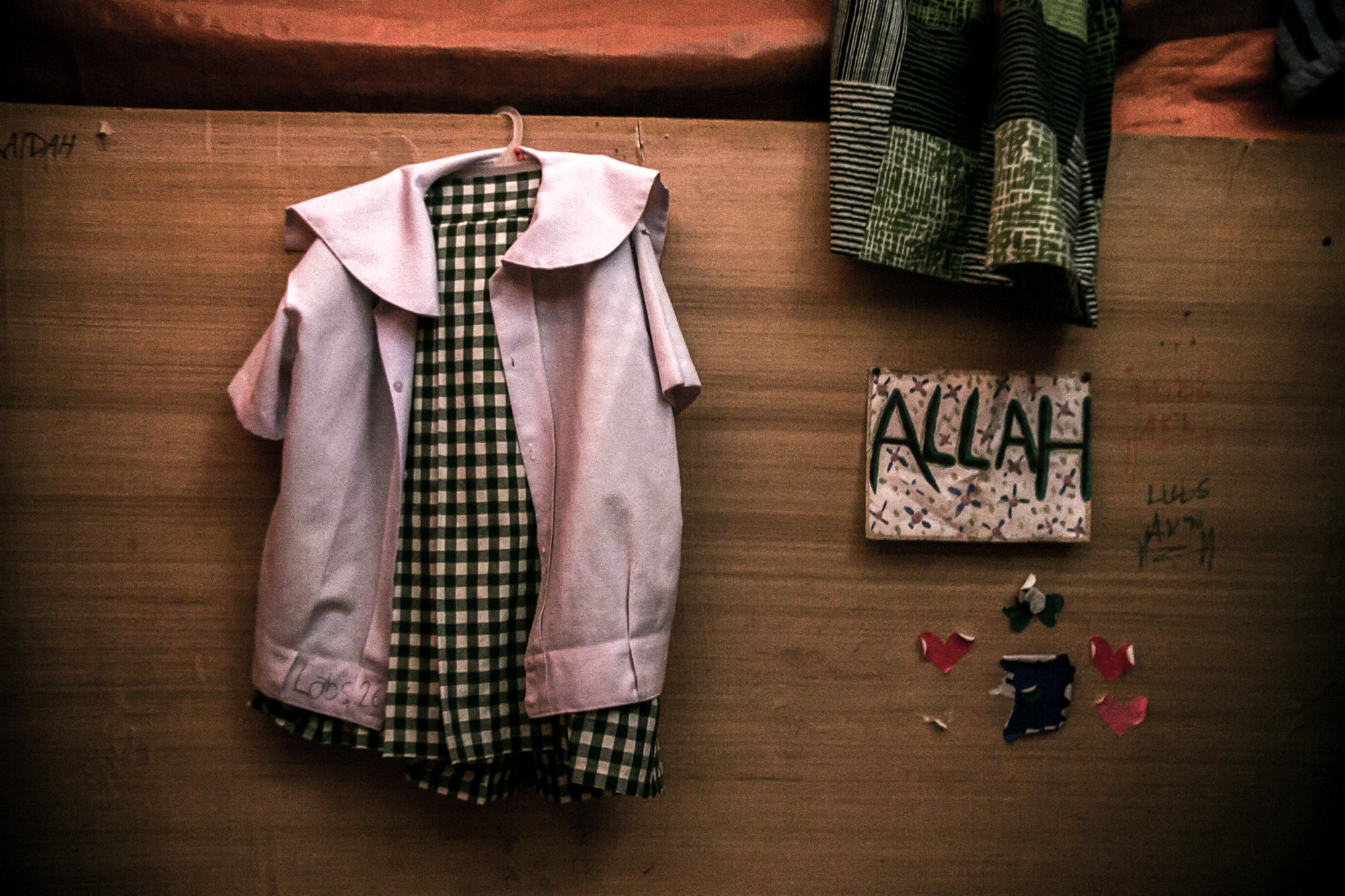 Fatima's school uniform hanging on a plywood wall of her cubicle. Each family is assigned to cubicle made of tarpaulins, blankets, and flimsy plywoods.