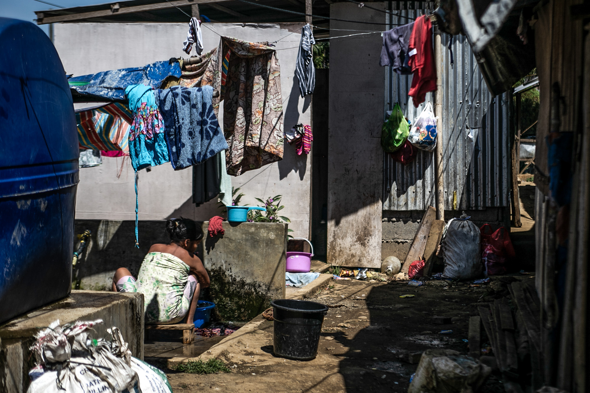 A woman does her laundry in an exposed area near the bathroom stalls inside the evacuation center in Saguiaran, Lanao del Sur. Women IDPs are at risk of gender-based violence because toilets and bath areas are not gender-segregated.