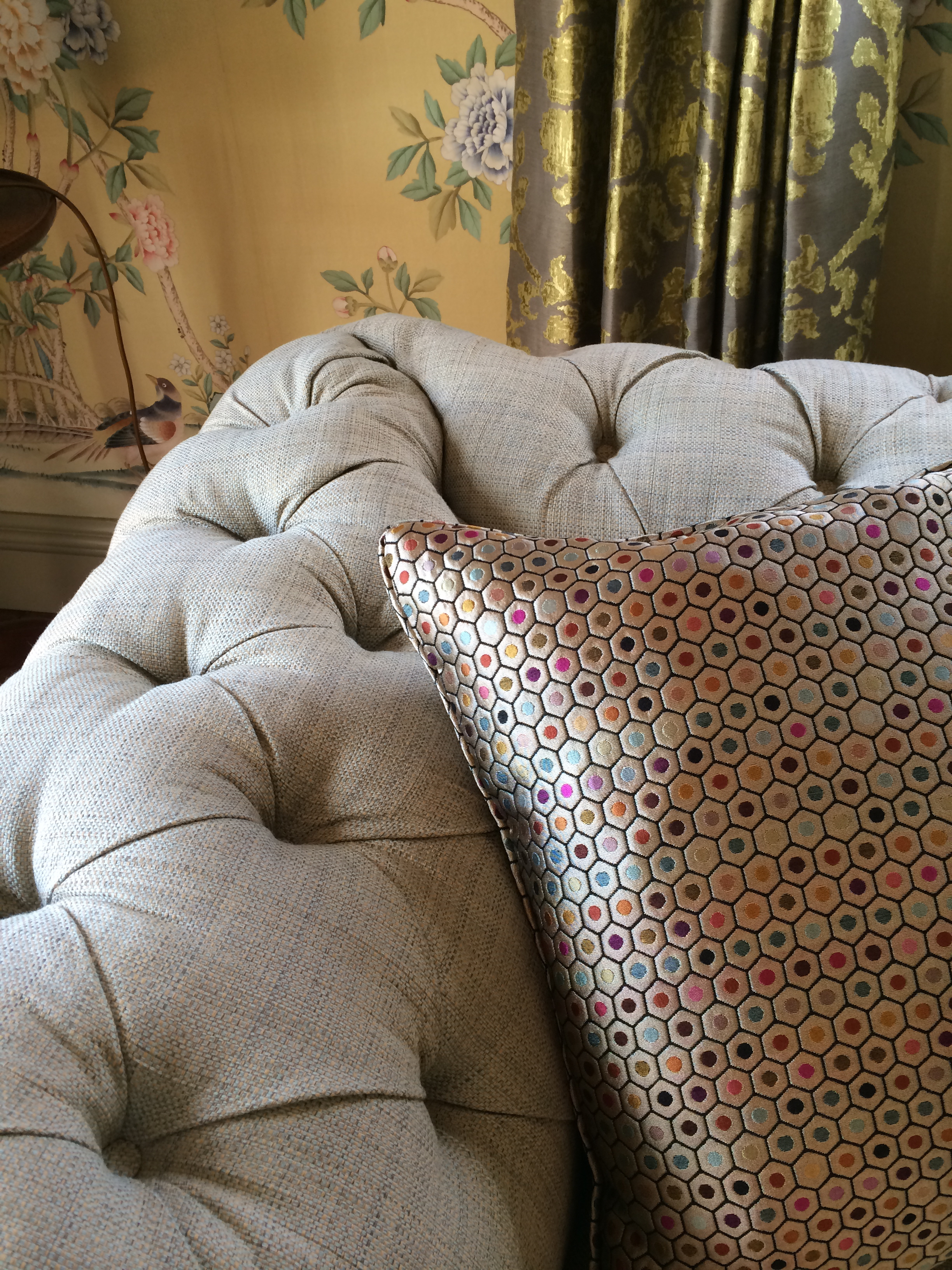 Traditional interior with a quirky touch. Detail of a chesterfield sofa and geometric print cushion and hand-painted silk wallpaper in the background.
