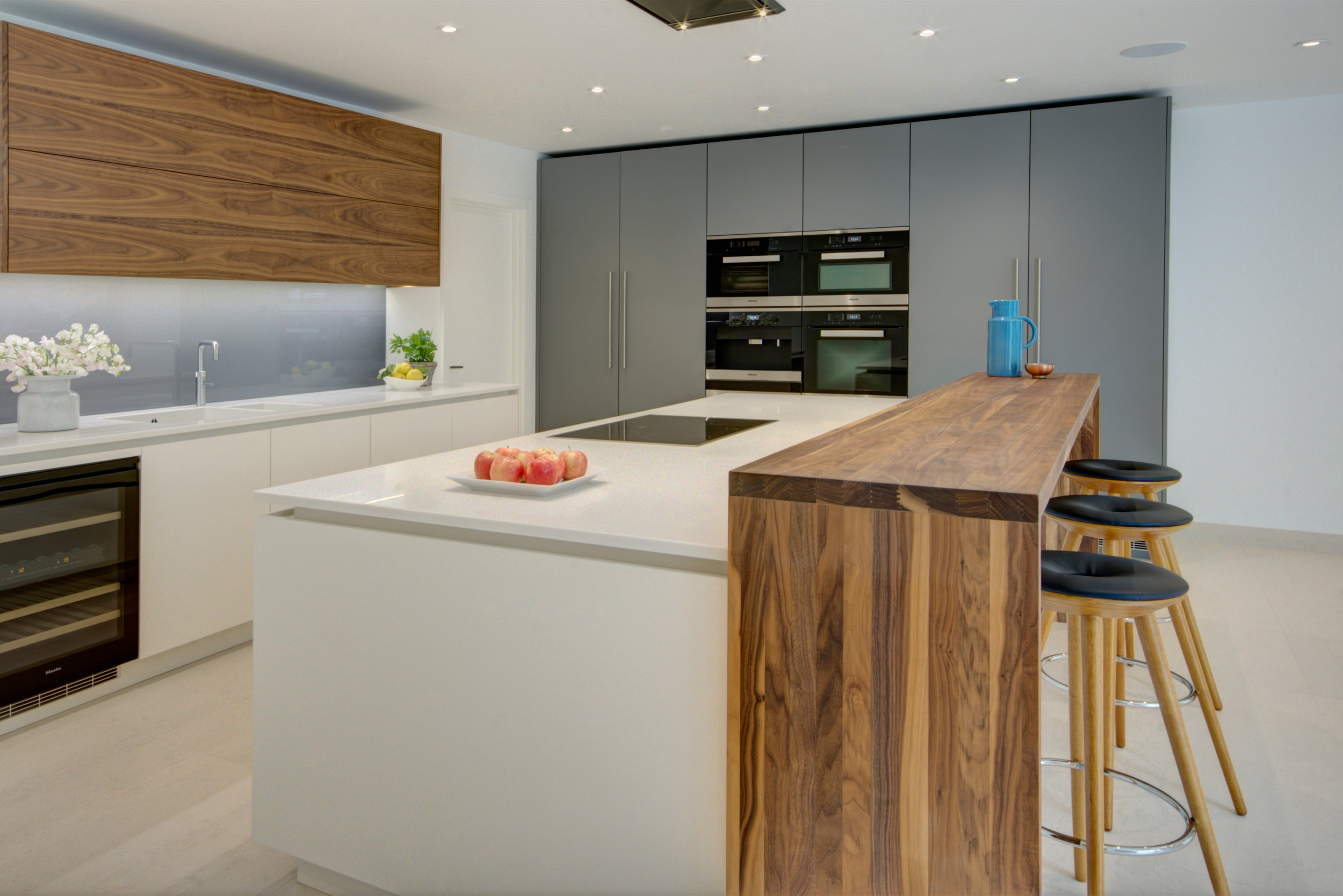 Contemporary kitchen design for a modern development with light coloured painted base units, walnut wall units and bar.