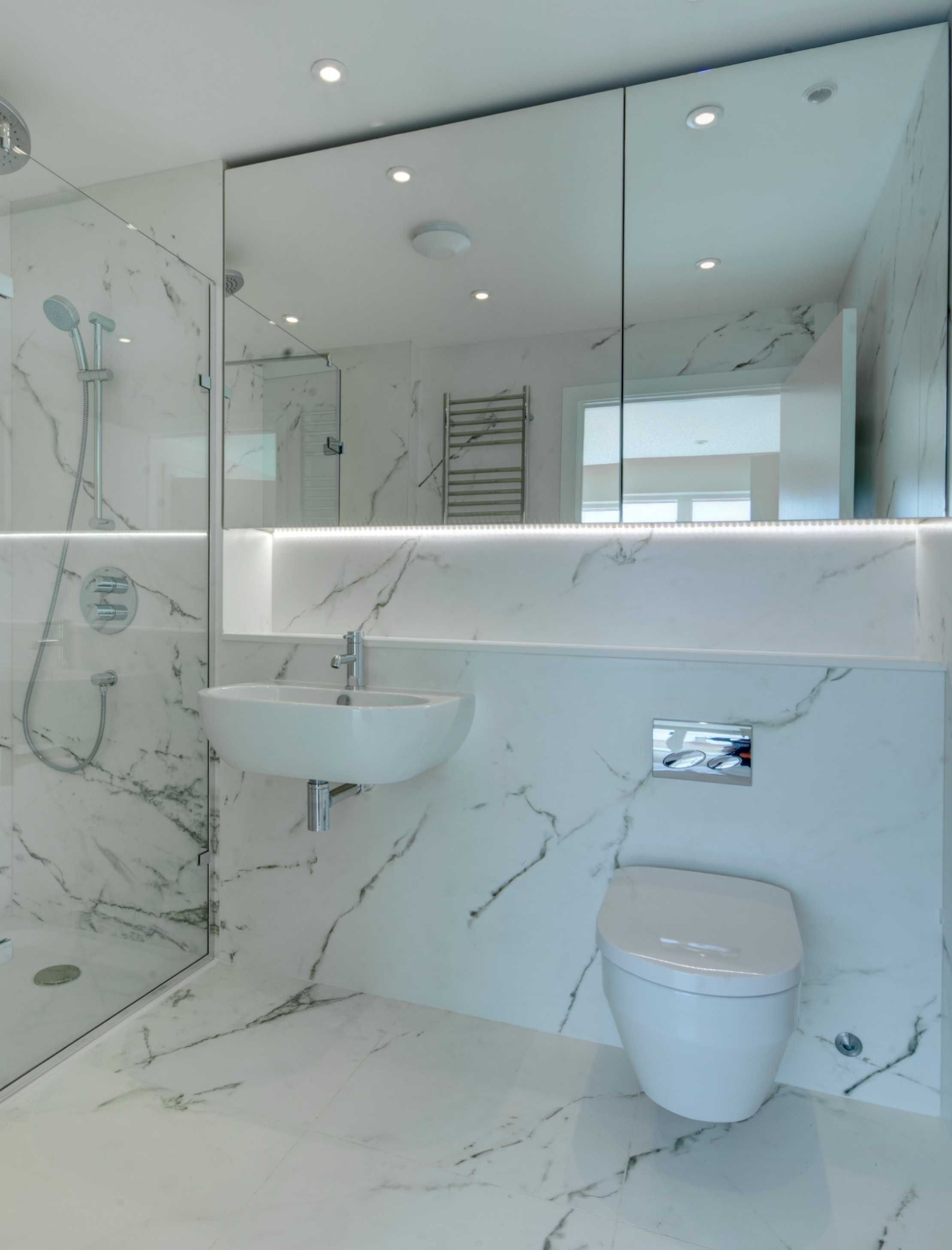 Bathroom design with marble effect wall finish and bespoke mirror cabinet.