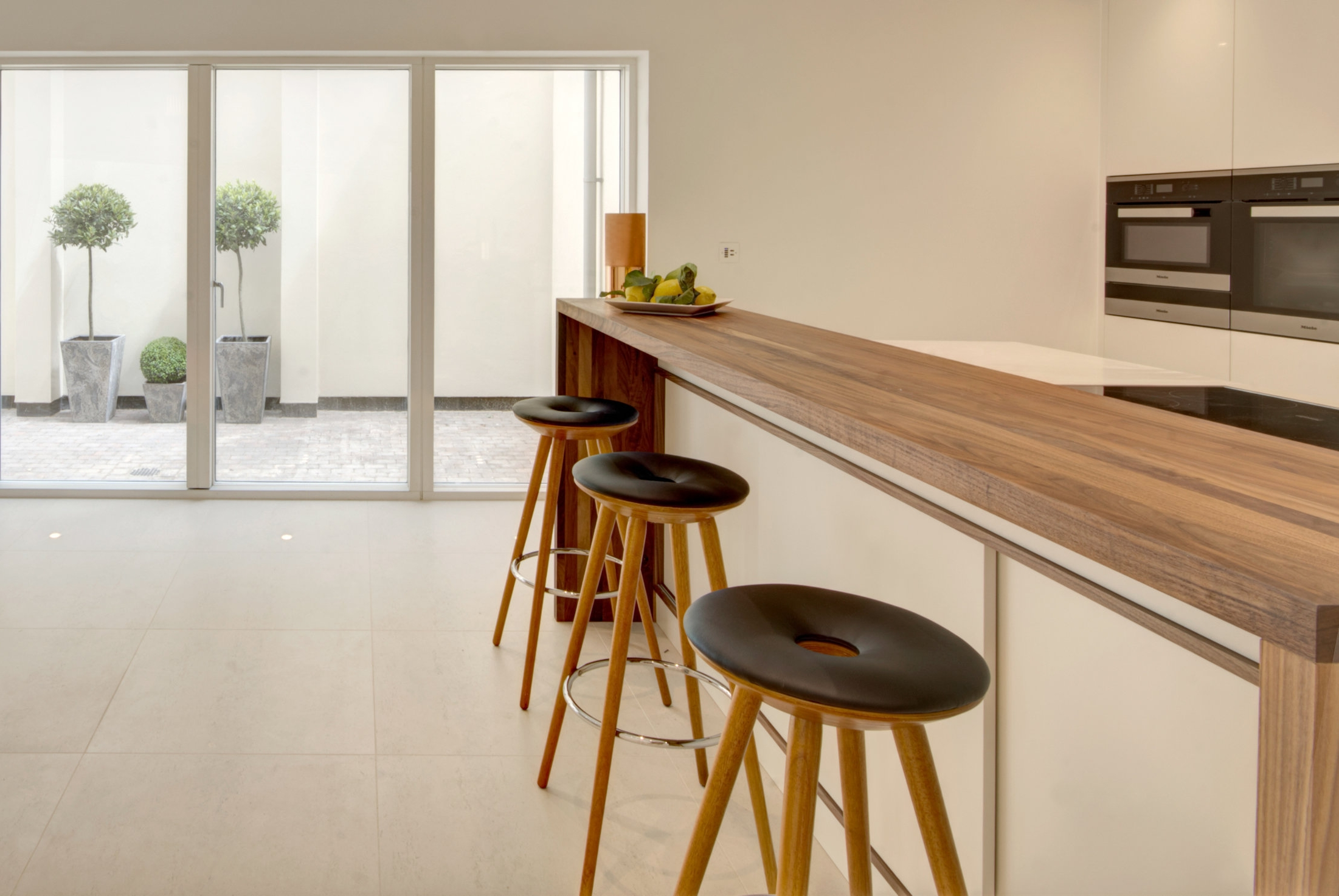 Kitchen design for contemporary development featuring island unit with walnut bar.