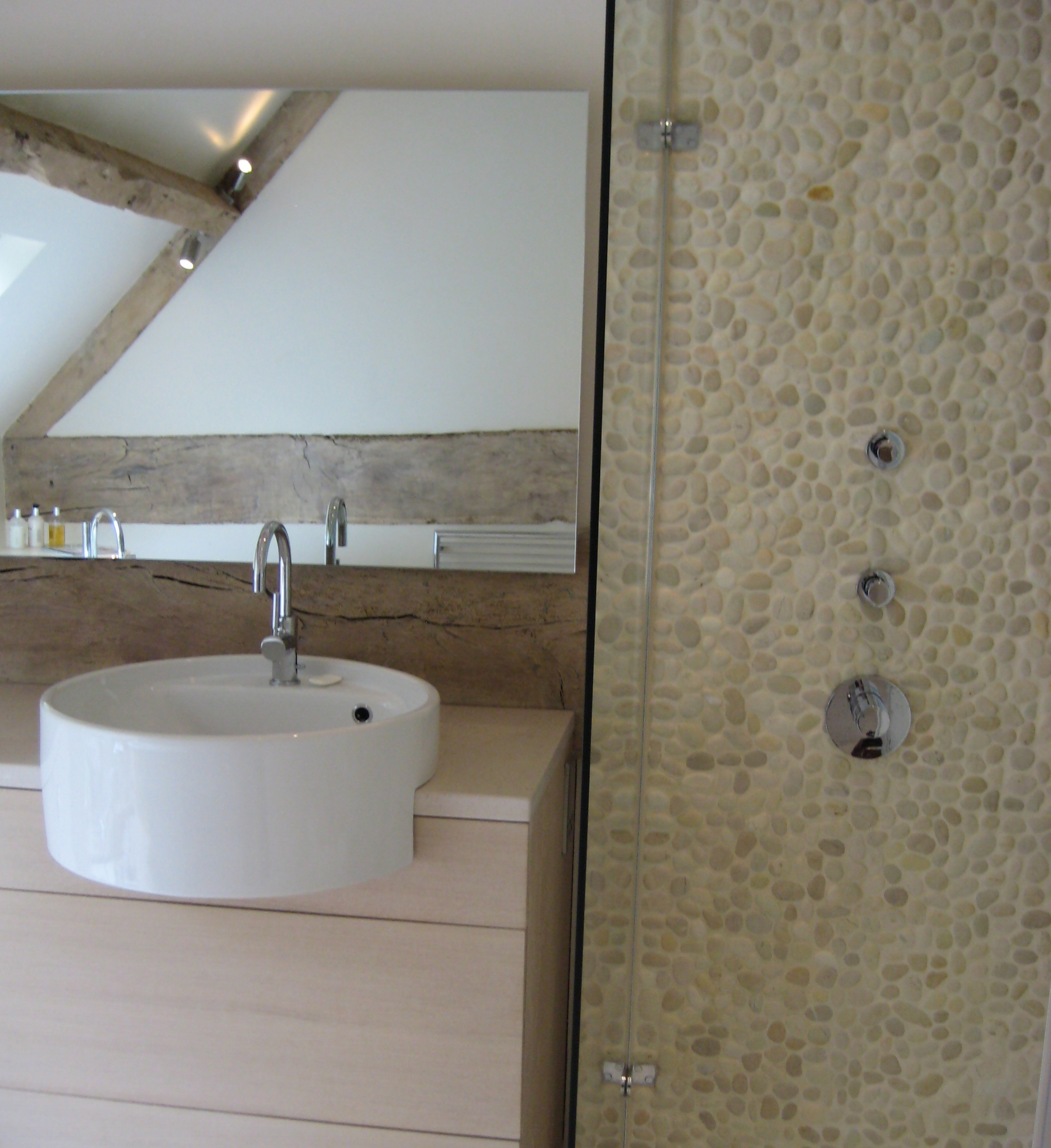 Contemporary bathroom design with semi inset basin and feature shower cubicle with pebbles.