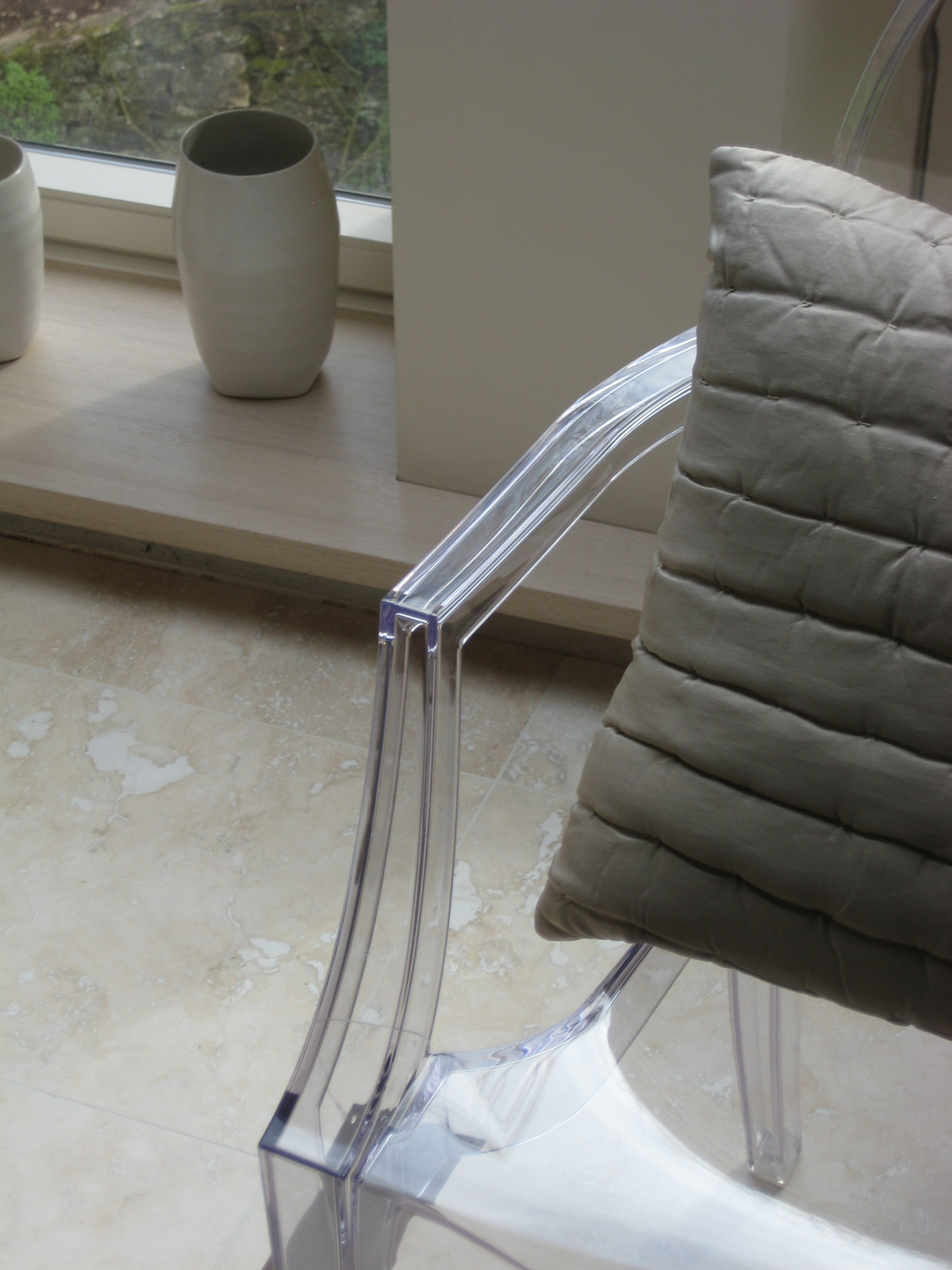 Detail of modern perspex chair with cushion and vase.