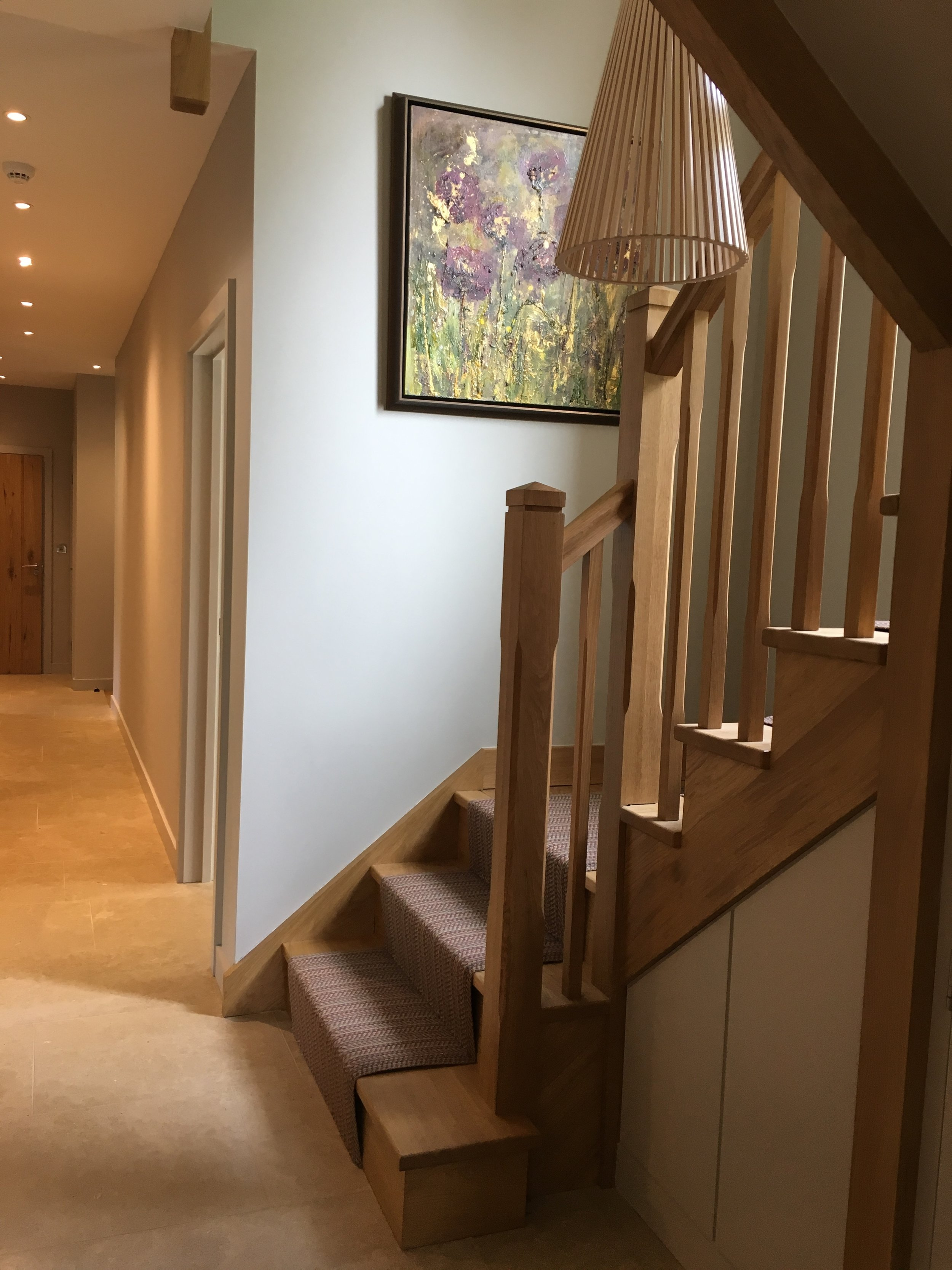 Oak staircase with runner, modern timber pendant light and oil painting.