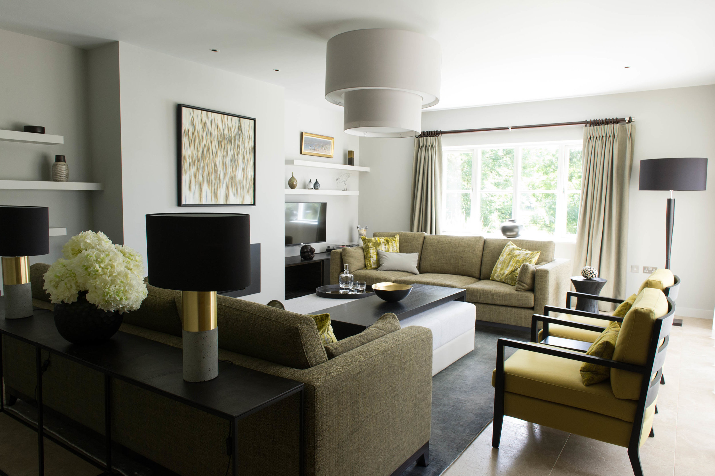 Sitting room in chartreuse tones with console table dressed with vase of hydrangeas and concrete and brass table lamps, pair of sofas, pair of armchairs, ottoman with bespoke coffee table, side table and floor lamp.By Joseph Interior Design, Cheltenham.