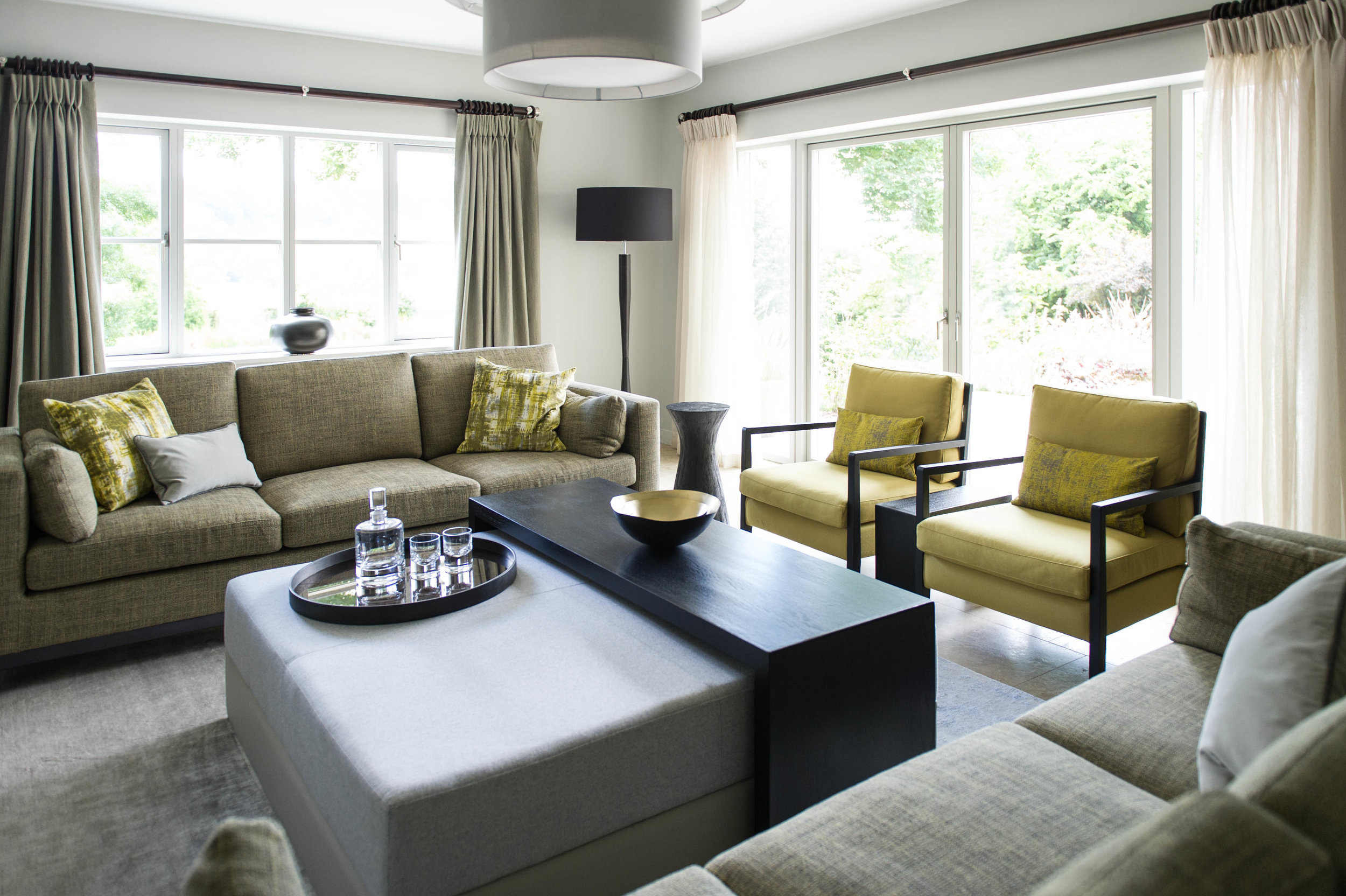 Sitting room in chartreuse tones with pair of sofas dressed with chartreuse and grey cushions, pair of armchairs, ottoman with bespoke coffee table, side table and floor lamp.By Joseph Interior Design, Cheltenham.