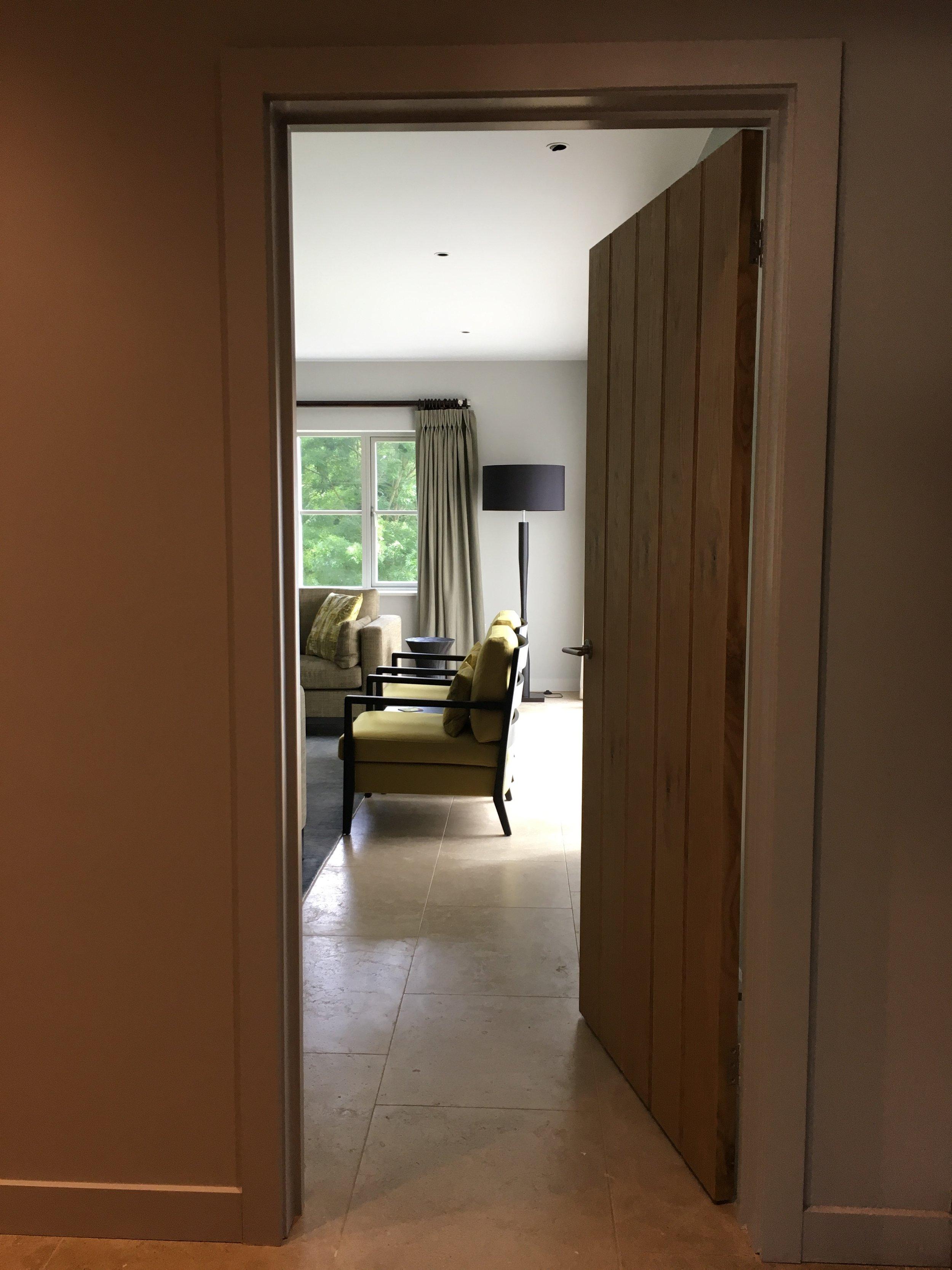 View of contemporary armchairs through a doorway. By Joseph Interior Design, Cheltenham.