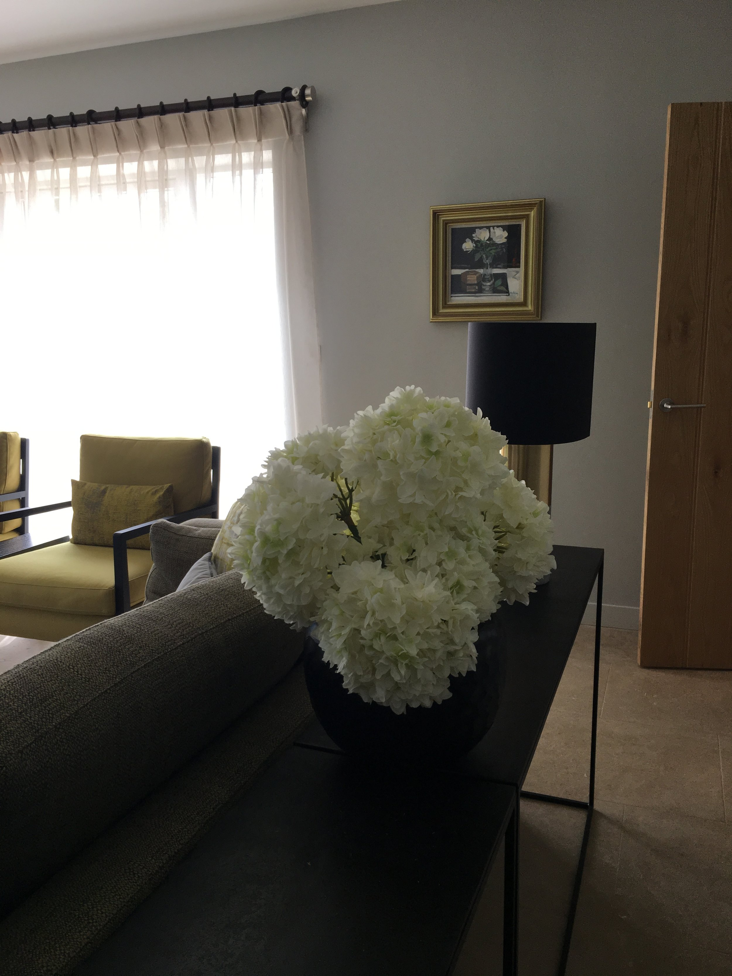 White faux hydrangea's on console table.