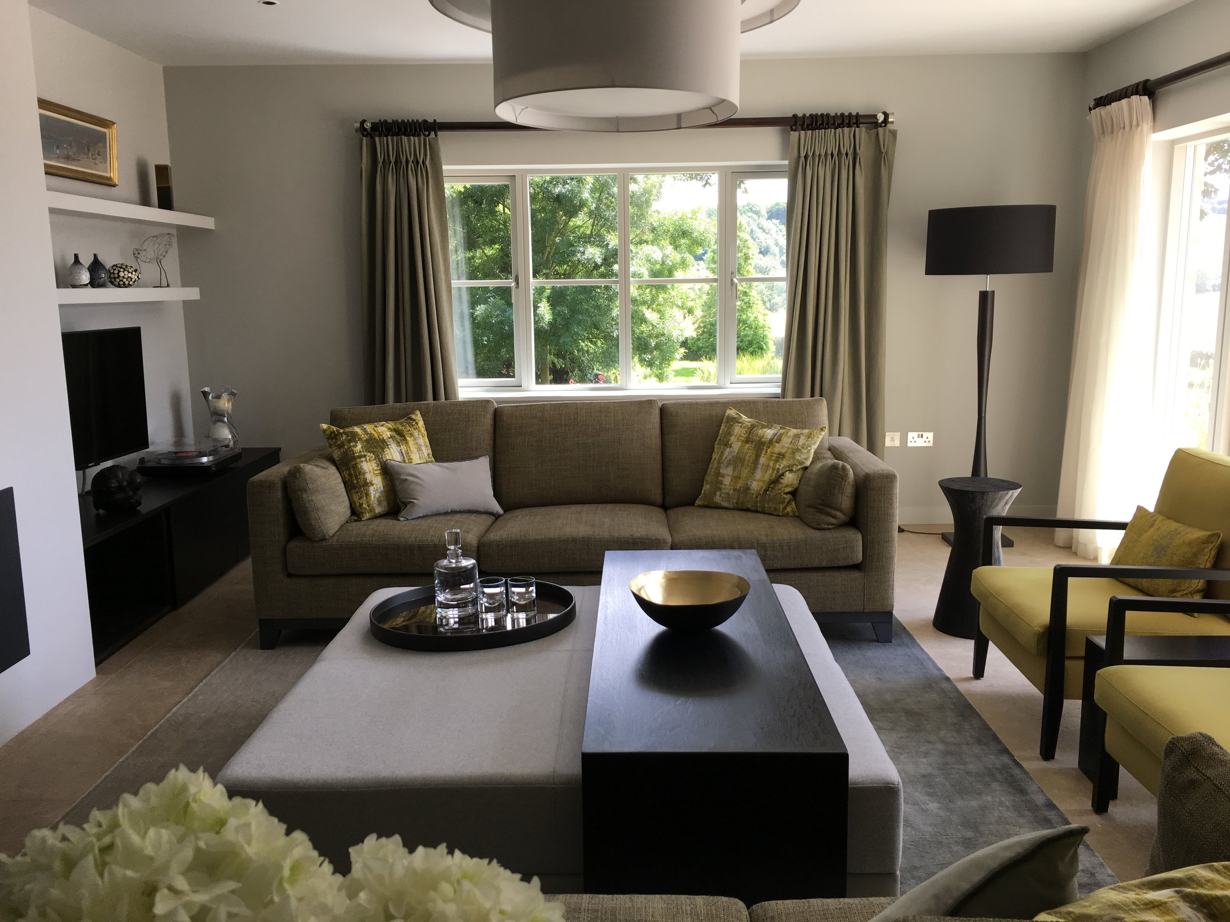 Classic, contemporary sitting room in chartreuse tones with sofa, floor lamp, armchairs, side table, bespoke ottoman and coffee table.By Joseph Interior Design, Cheltenham.