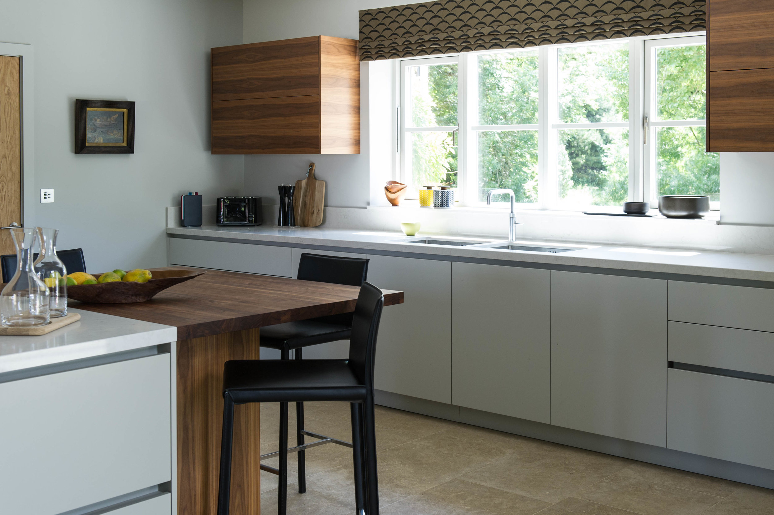 Kitchen design with painted base units, walnut wall units and island unit with bar stools.