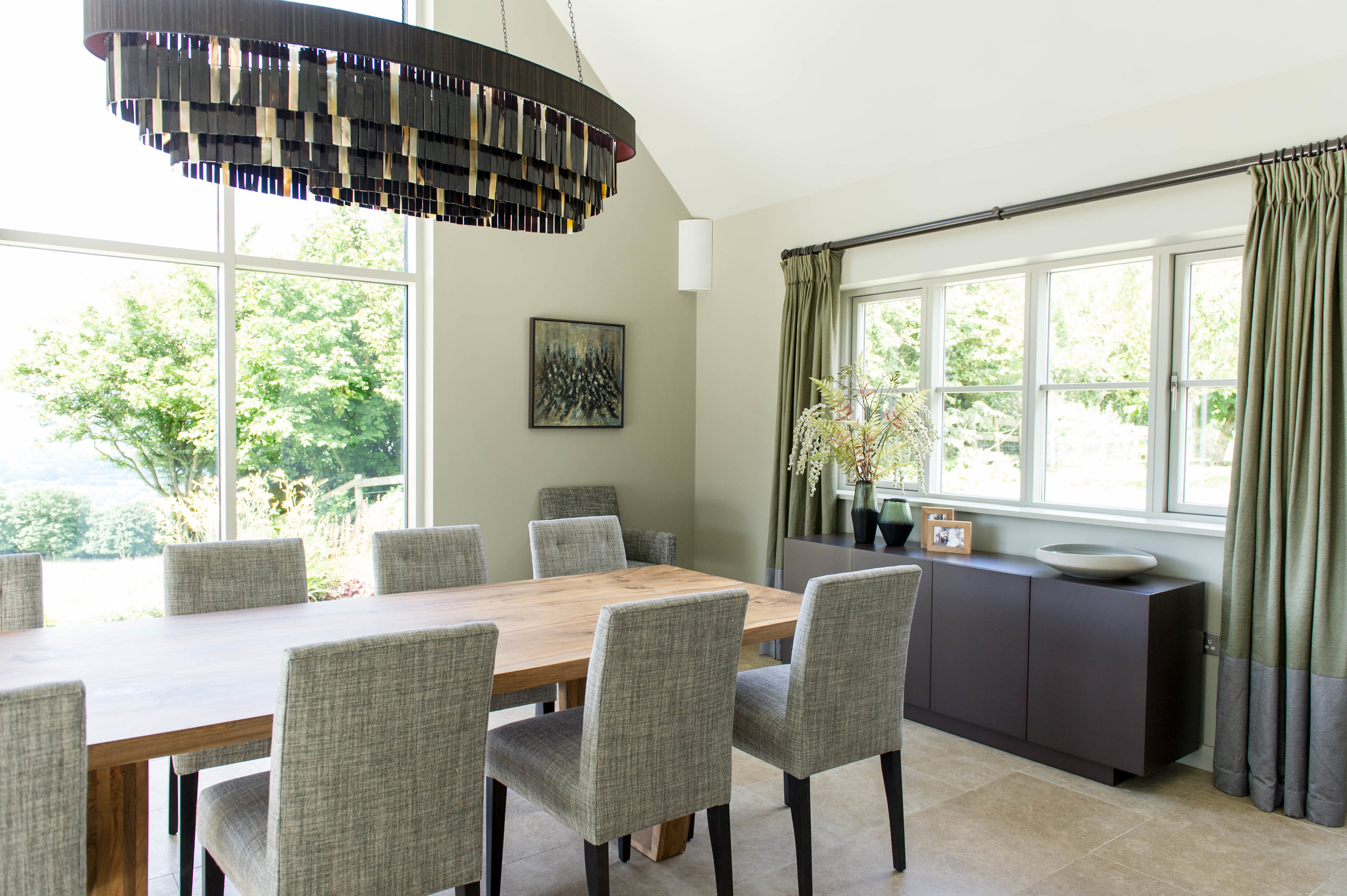 Dining room with timber dining table, grey upholstered chairs, dark lacquered sideboard, contemporary chandelier and two-tone curtains. By Joseph Interior Design, Cheltenham.