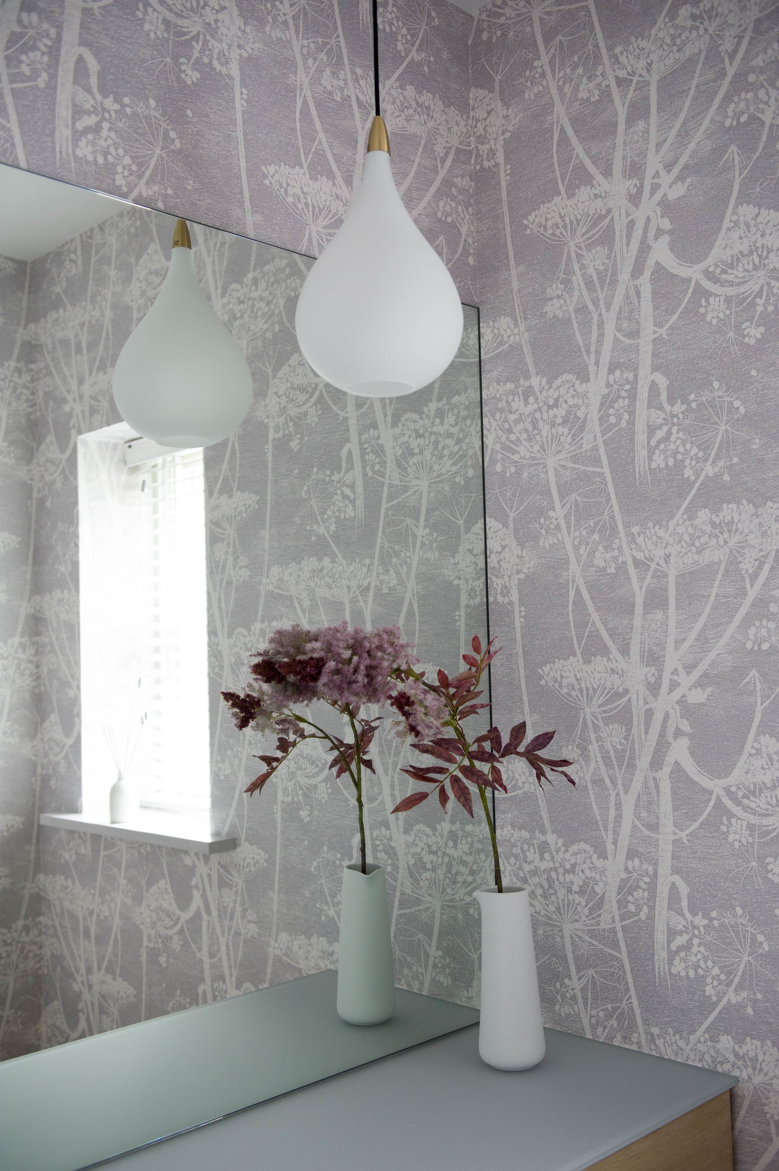 Bathroom design with pretty, botanical wallpaper and vase of flowers.