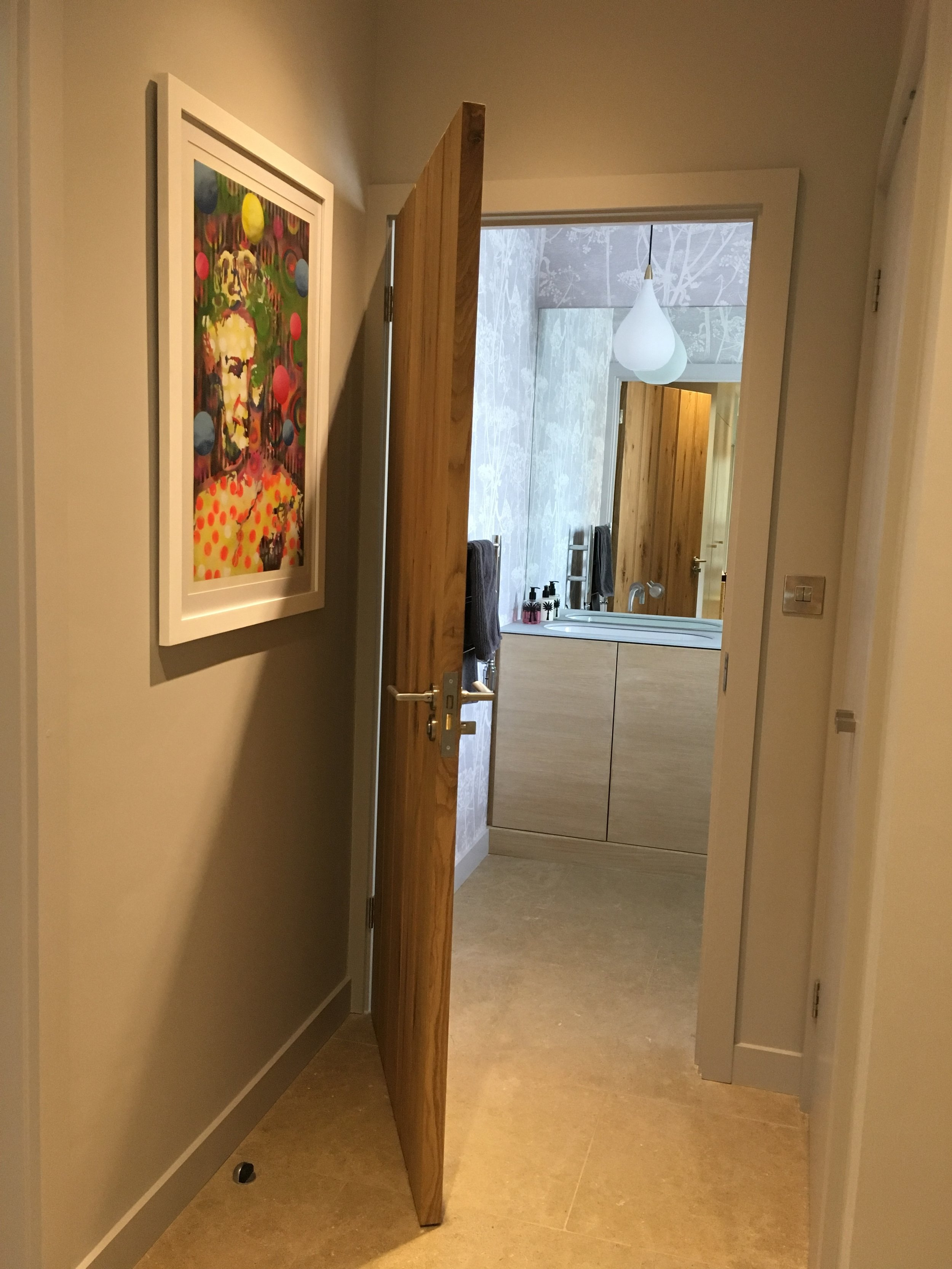 View into cloakroom through doorway. Contemporary artwork on wall.