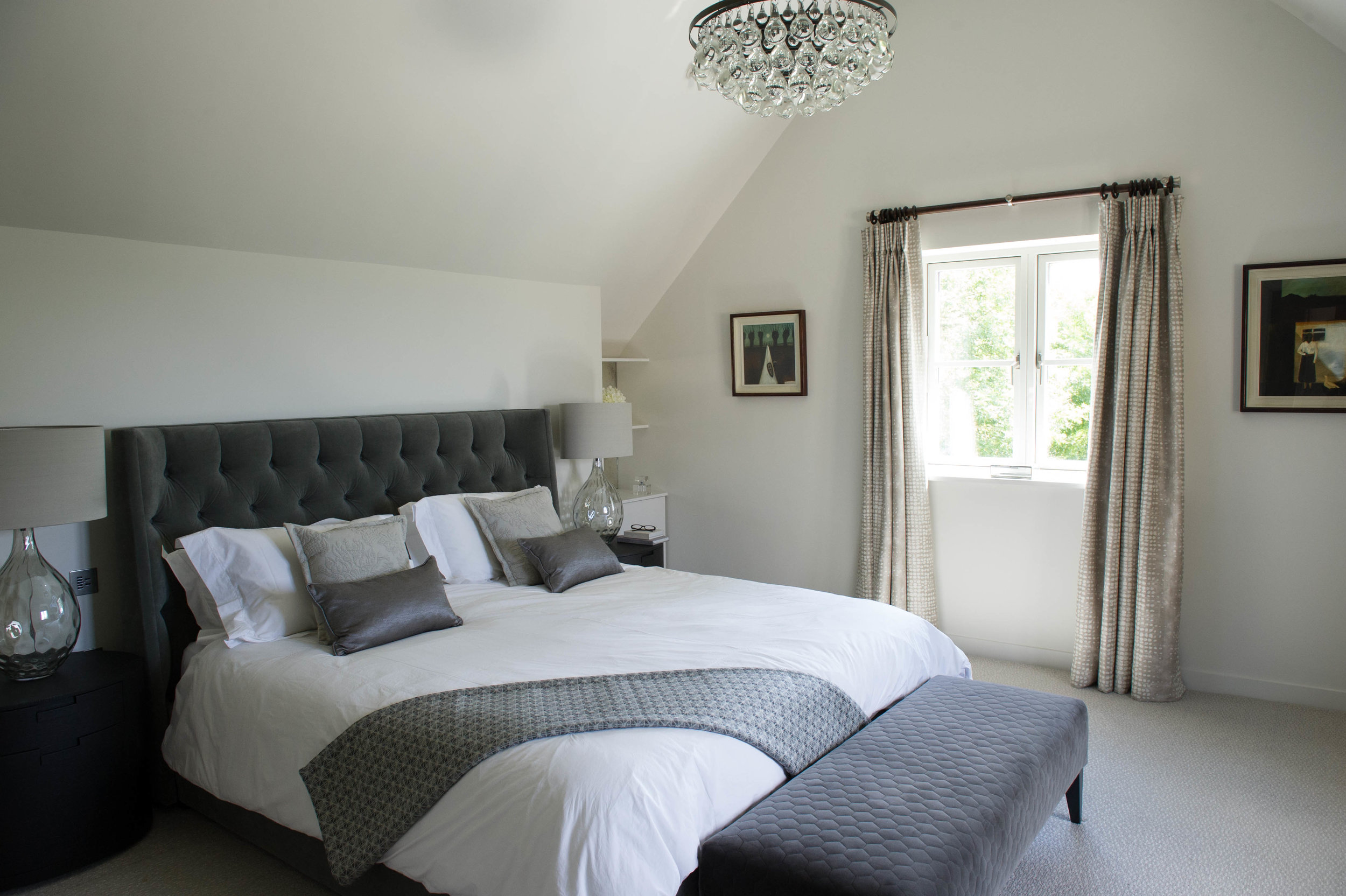 Master bedroom in grey tones with glass table lamps, quilted bench, contemporary glass chandelier and upholstered bed dressed with cushions and throw. By Joseph Interior Design, Cheltenham.