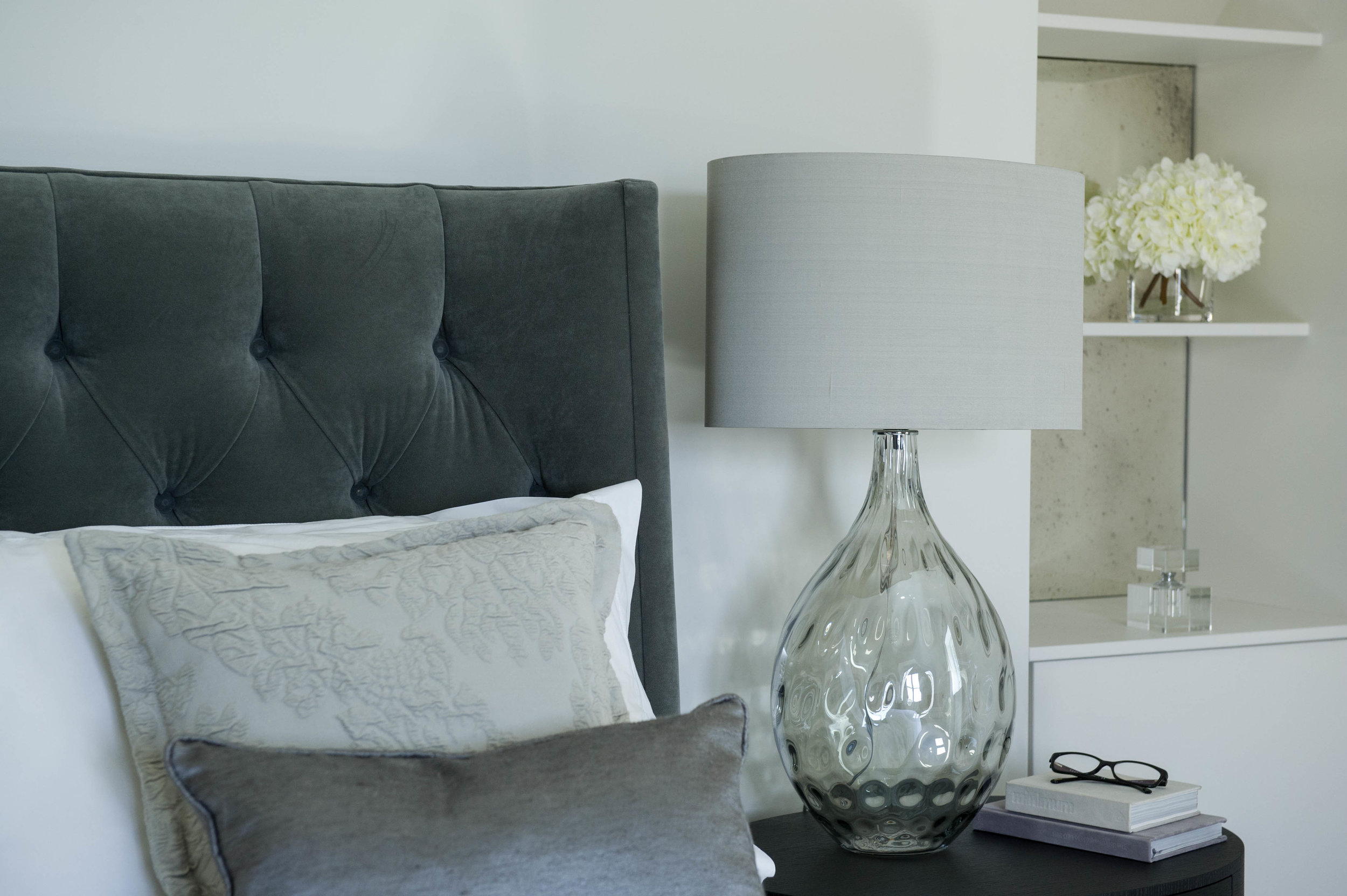 Detail of glass table lamp, cushions and mirrored alcoves dressed with vase of white hydrangea's and perfume bottle.