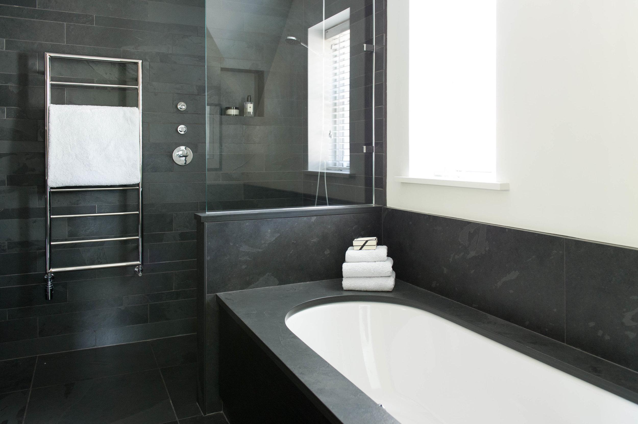 Bathroom design with black slate tiles, inset bath and walk-in shower.