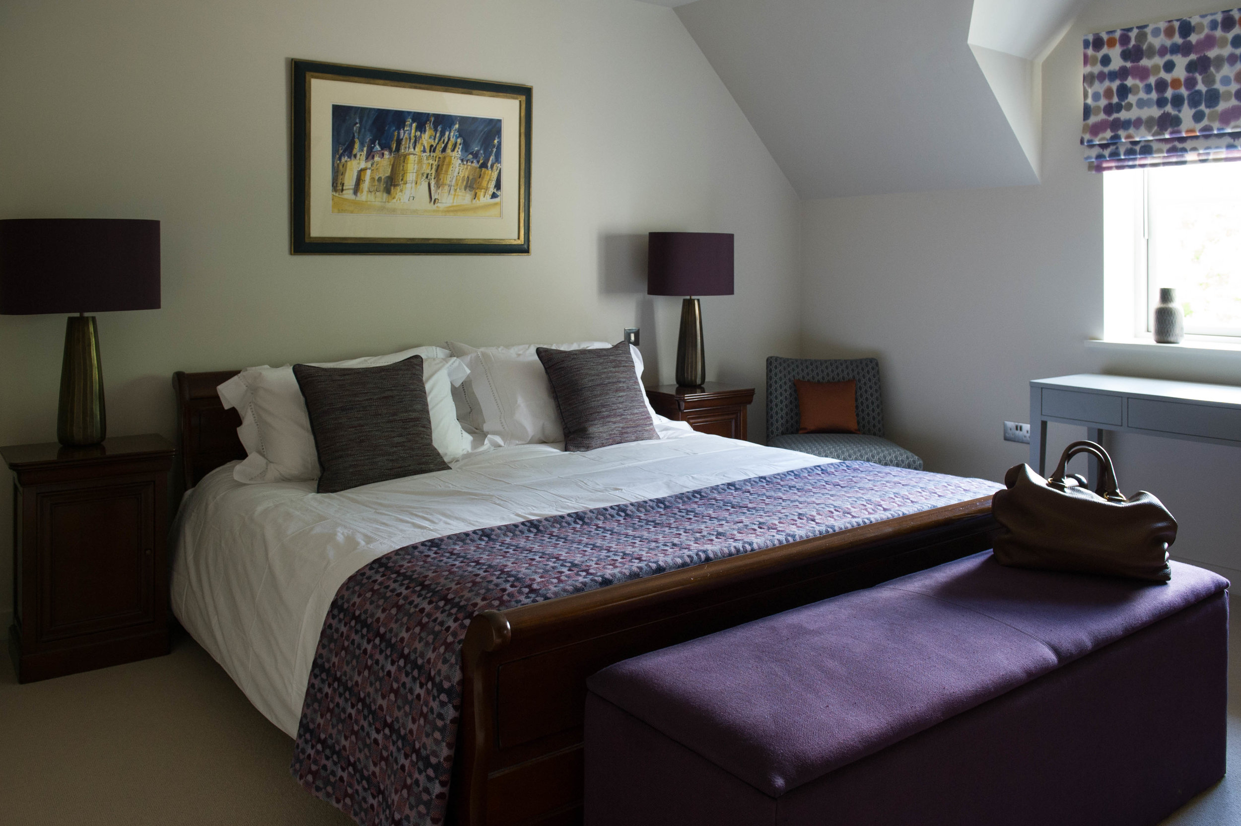 Bedroom in purple and blue tones with orange accents. Timber sleigh bed and bedside tables with table lamps, blanket box, bedroom chair and dressing table. By Joseph Interior Design, Cheltenham.