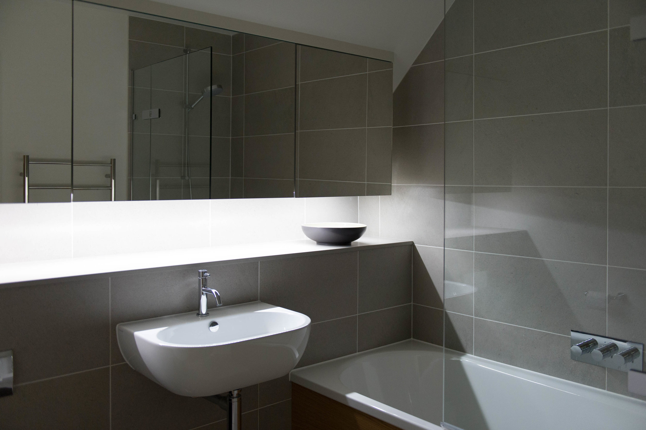 Contemporary bathroom design with white basin and bath, large format grey tiles and bespoke mirrored cabinet.
