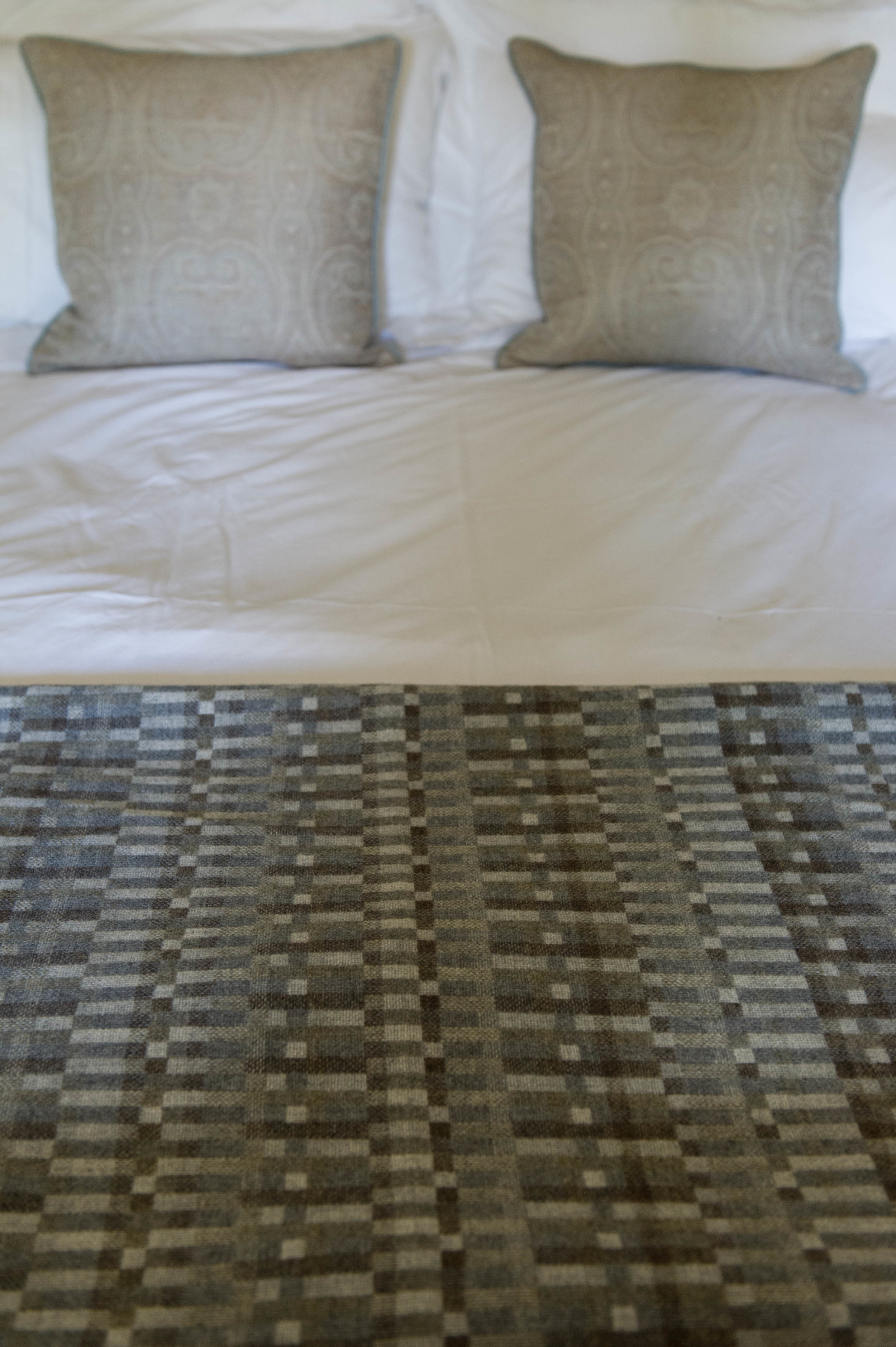 Bed dressed with grey, check throw and paisley print cushions.