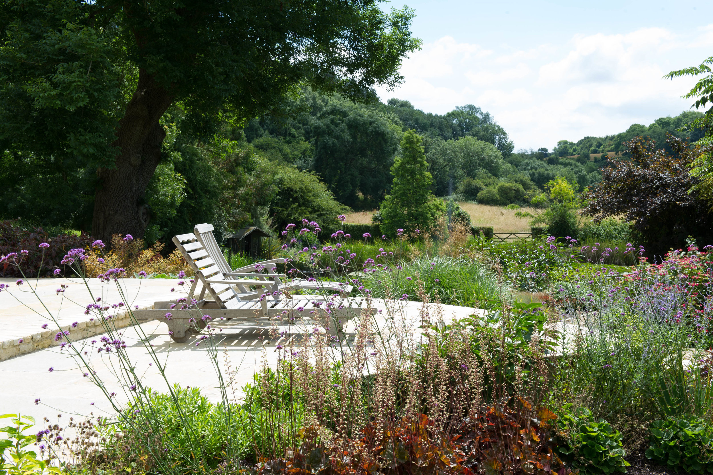 View of the Cotswold landscape from deck with timber sun loungers.