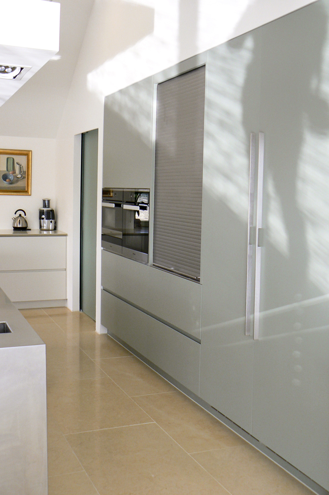 Kitchen design with grey-green painted units, tambour unit and appliances.