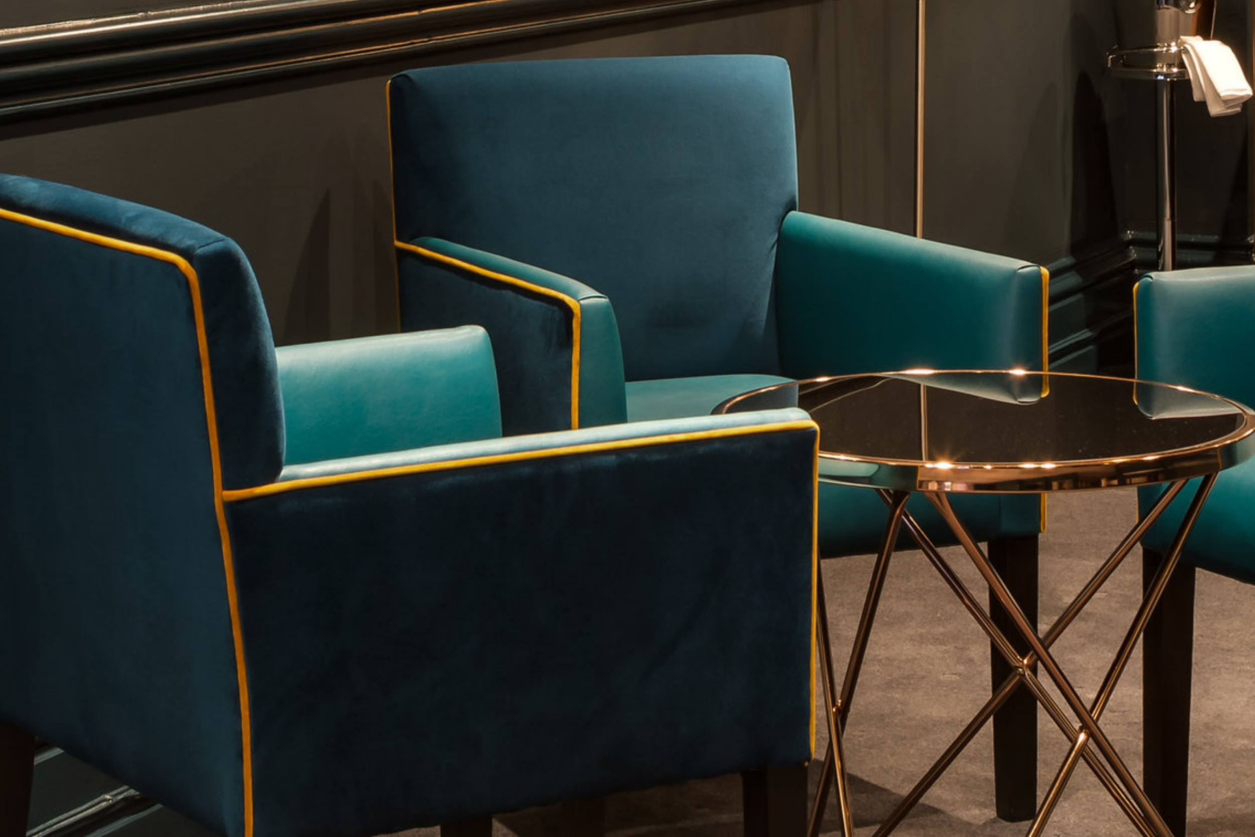 Detail of upholstered armchairs with brass table.