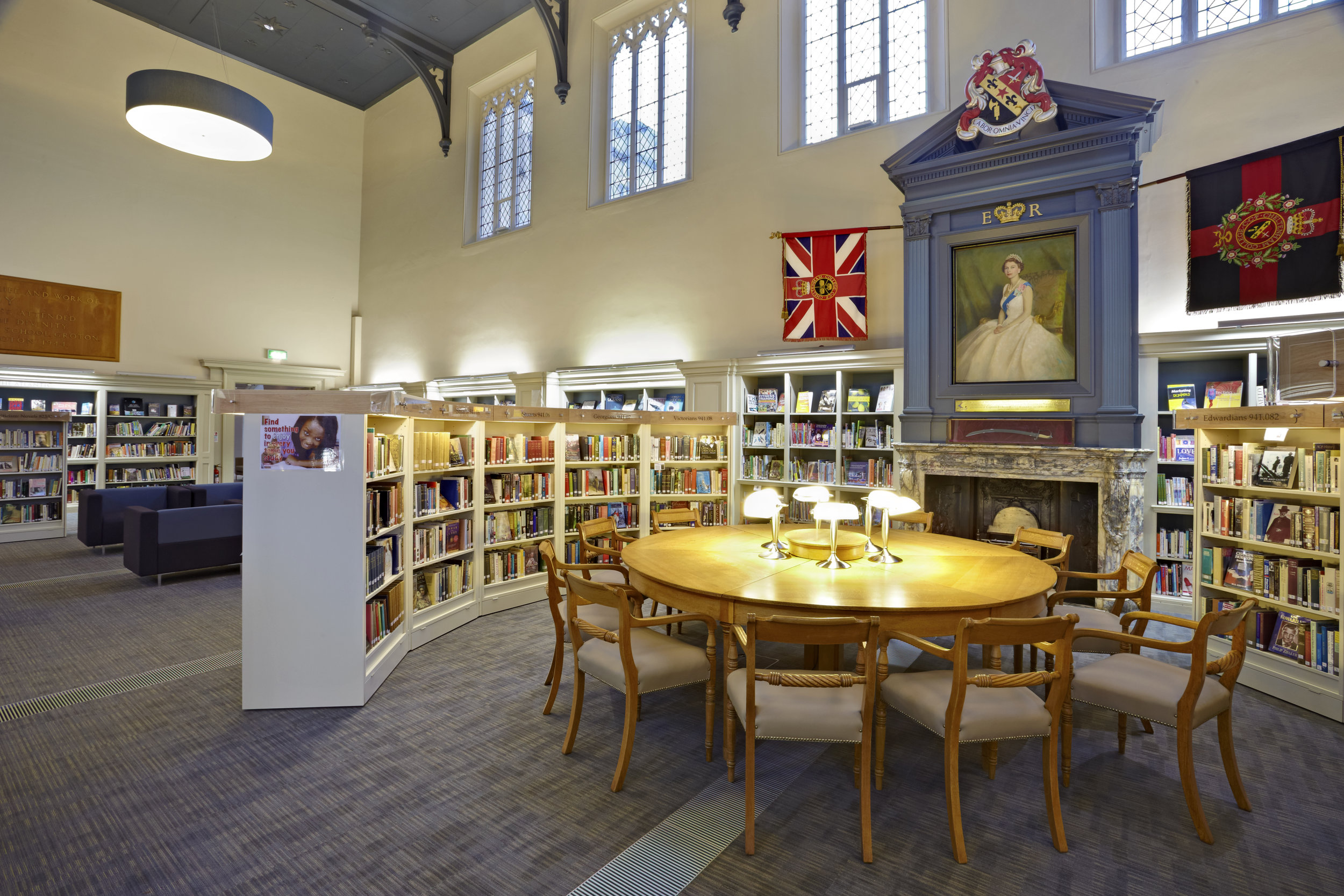 College library with bookshelves, table and seating.