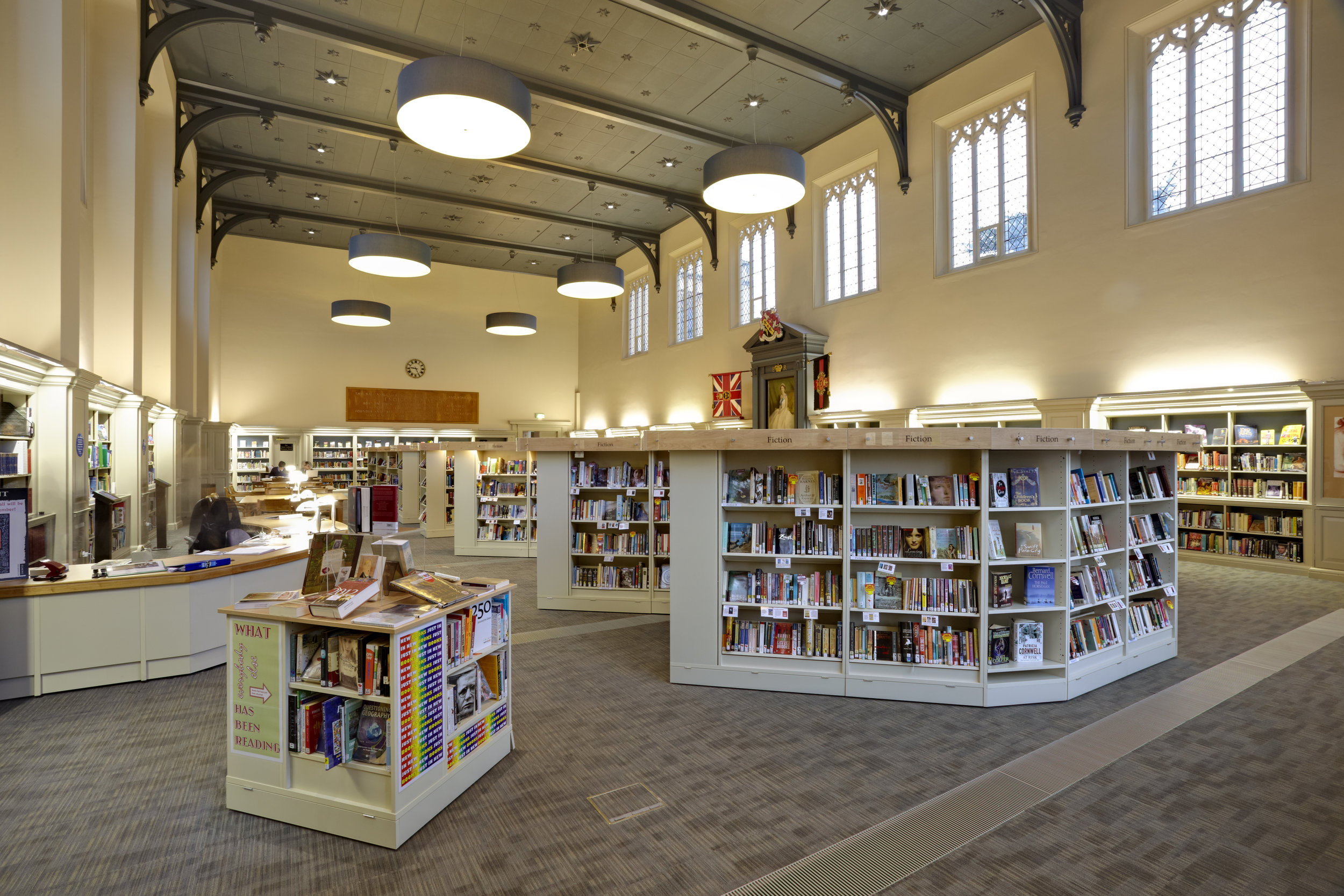 College library with bookshelves and large pendant lights.