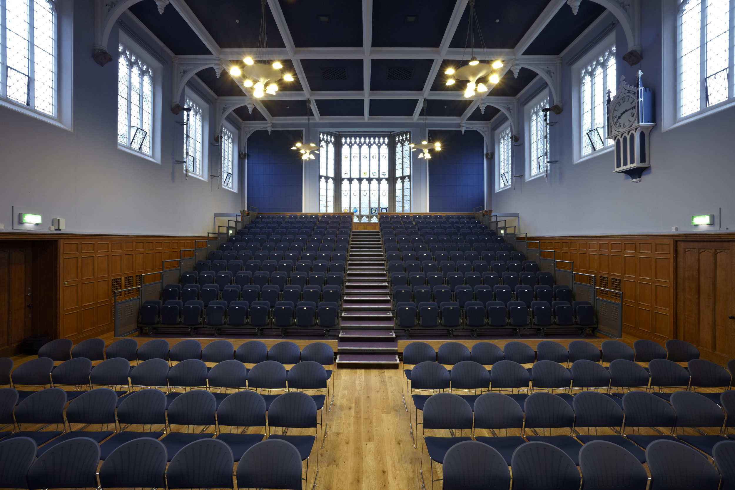 College lecture theatre with blue seating and wall colour and traditional wooden panelling.