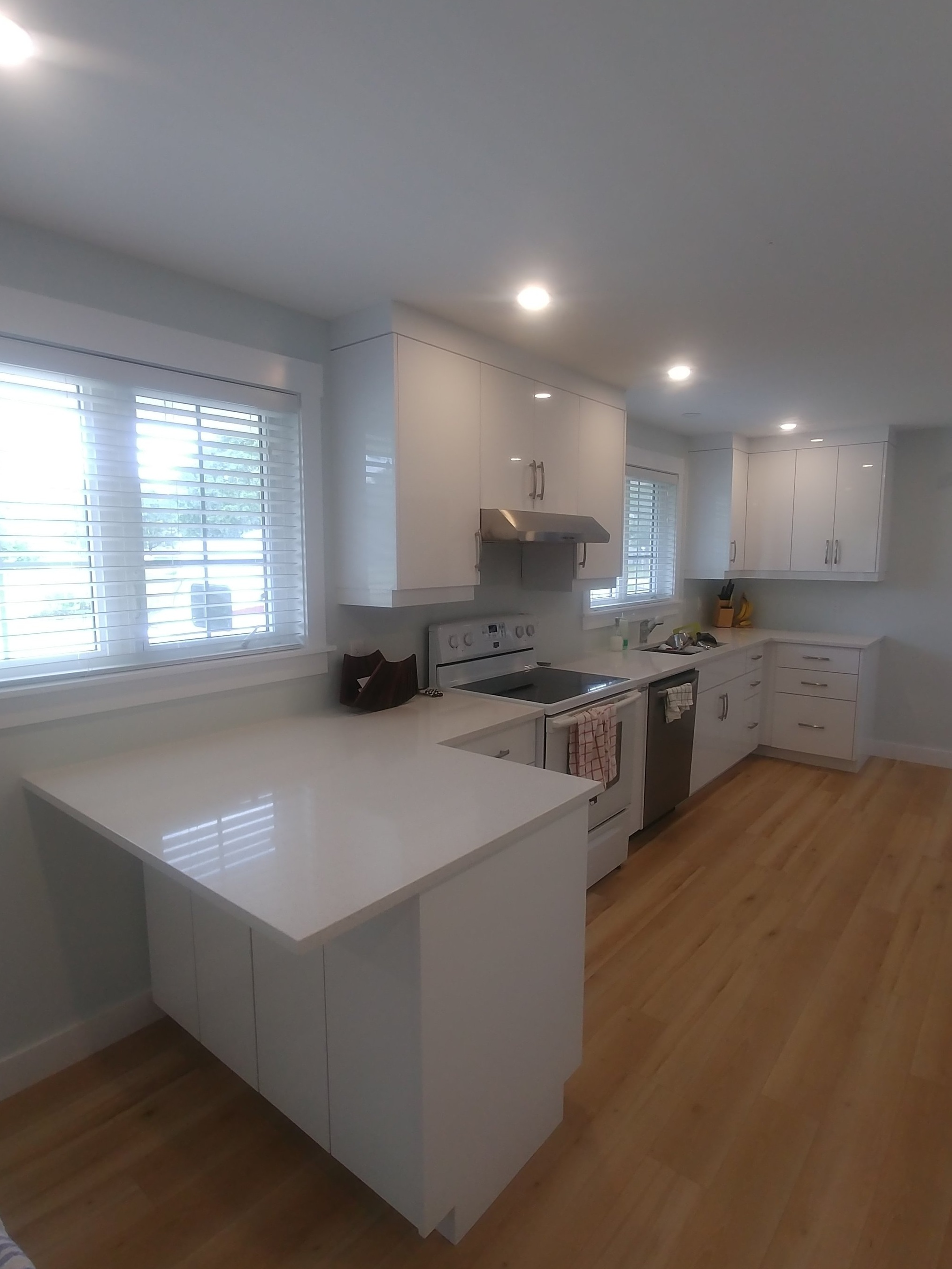 High gloss white panel doors and Blanco Maple quartz counter-top