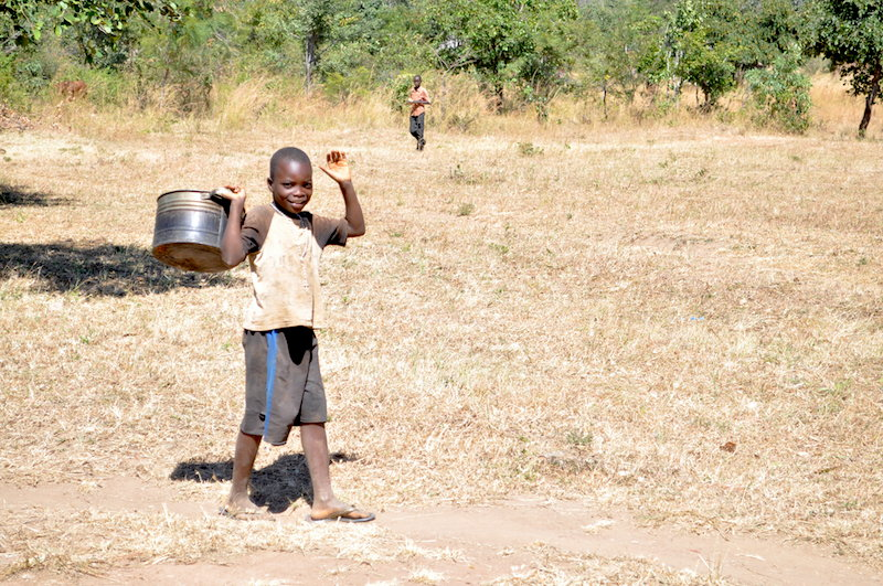 Young boy fetches water for cooking in Cohombe Village