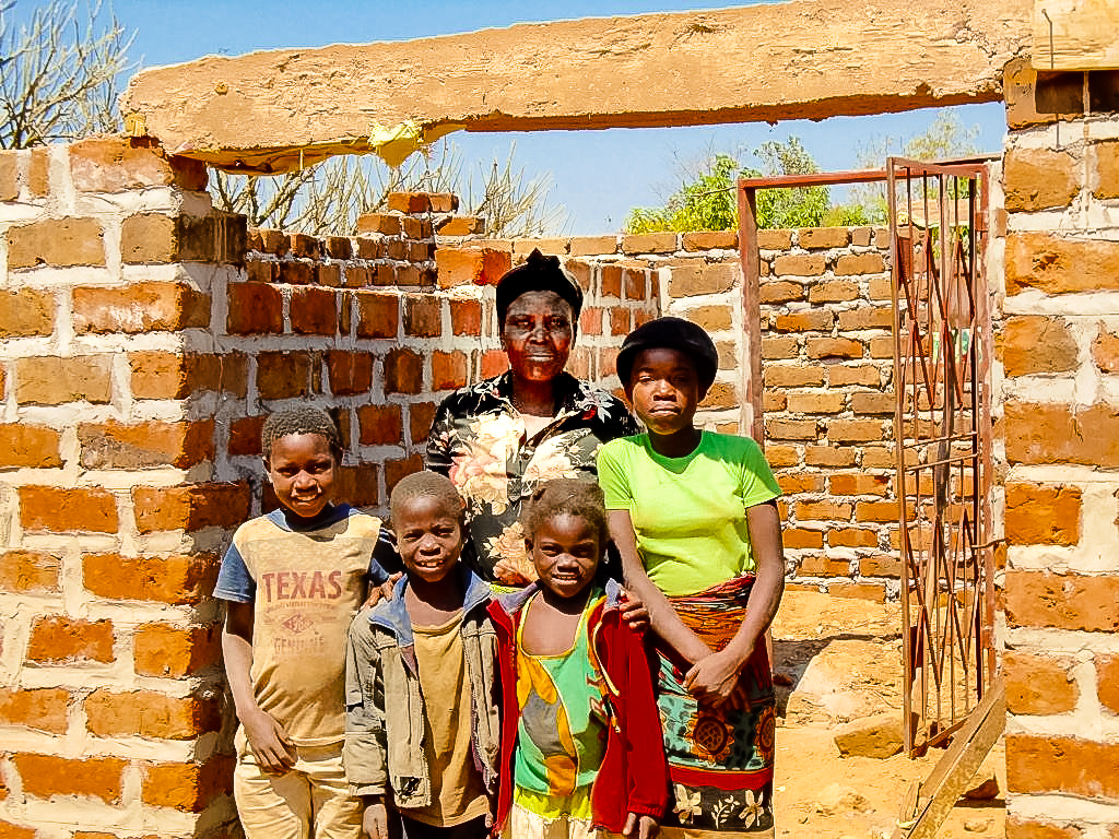 Martha stands in front of her partially built home with grandkids. After putting construction aside for some years - Martha has saved enough money to start building again.
