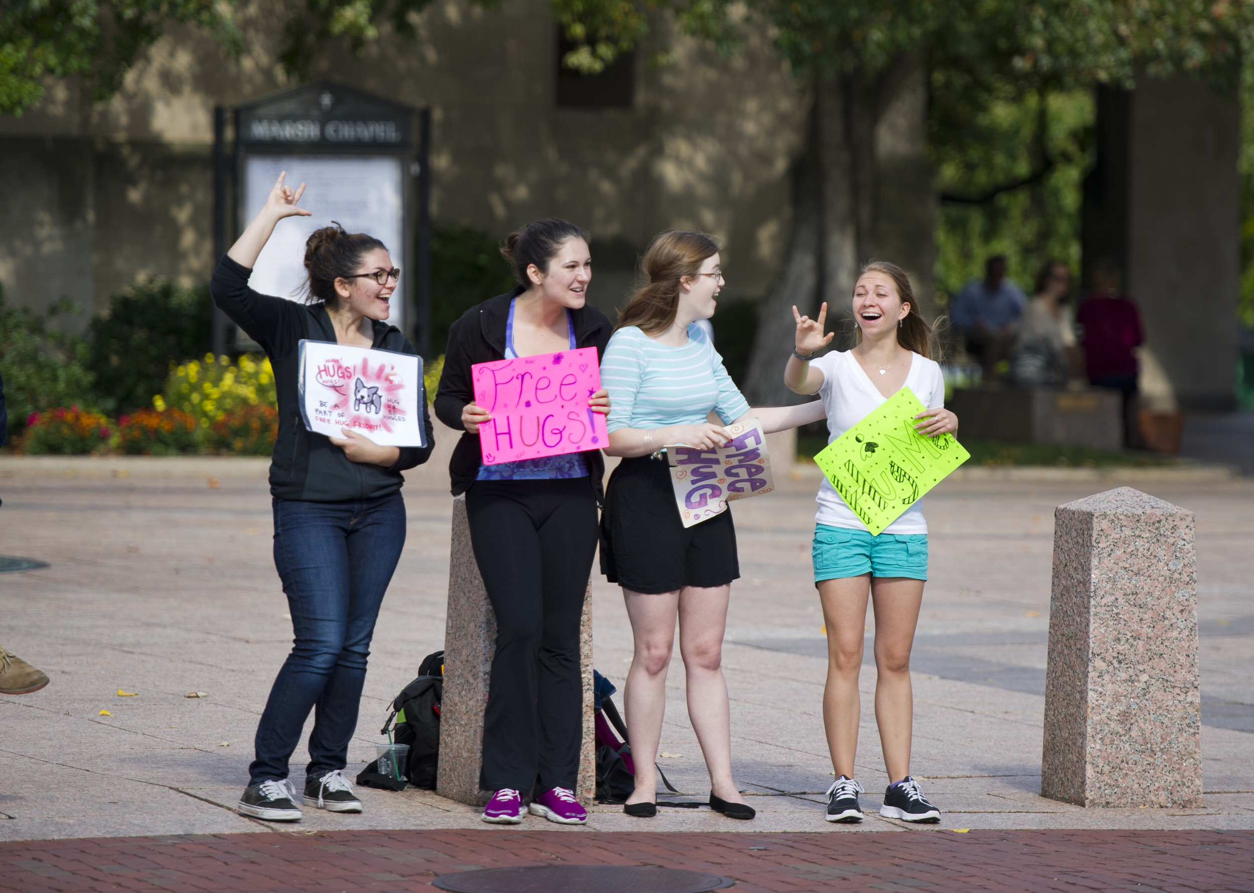"When a passerby flashes them the ASL sign for ""I love you"" I Embrace You president Melanie Kirsh (CAS'16), far left,  and Chelsea Hammond (SED17), far right, react by doing the same at Marsh Plaza October 17, 2014 . Between Kirsh and Hammond and also on hand to dole out some love were Taylor Adkin (SAR17), left, and  Courtney White (SAR17).  Photo by Cydney Scott for Boston University Photography"