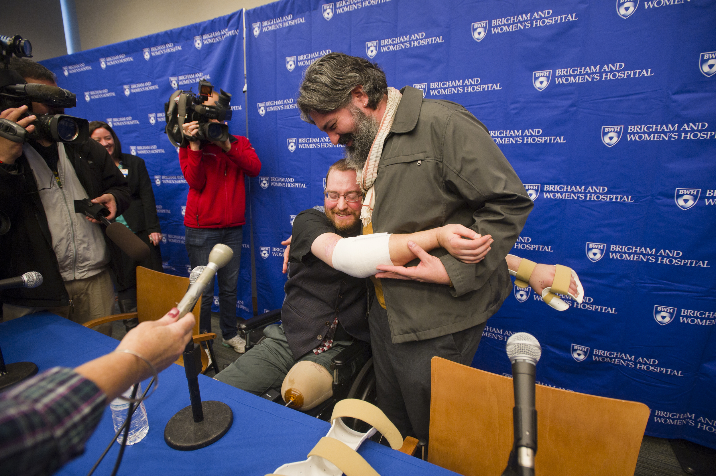 While he can't yet apply pressure to his arms, Will Lautzenheiser is still happy to demonstrate how he can now hug his partner Angle Gonzalez during a press conference to share the news of his successful bilateral arm transplant along with his surgeons Dr Matthew Carty, Dr. Simon Talbot, and Dr. Bohdan Pomahac (not pictured) at Brigham and Women's Hospital (BWH) November 25, 2014. Lautzenheiser, 40, who became a quad amputee in 2011 following a life threatening streptococcal infection received his new limbs from an anonymous donor in October.  Photo by Cydney Scott for Boston University Photography
