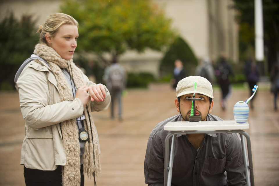 Ashley Short (SAR DPT,'12) looks on while Adrios Garcia (CAS,'15) balances a toothbrush on a cap to learn proper squat technique in Marsh Plaza October 26, 2011. Short and her classmates from Physical Therapy Management class had multiple tests and challenges set-up on the plaza to teach those participating about healthy habits for a strong back. October is Physical Therapy Awareness Month. Photo by Cydney Scott for Boston University Photography
